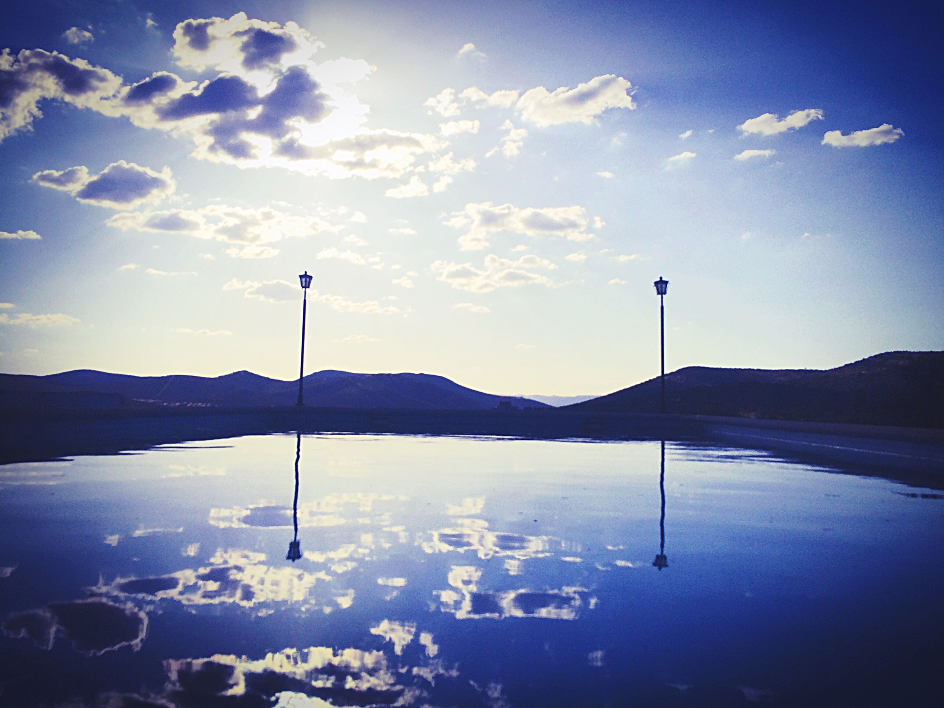 mountain, water, tranquility, tranquil scene, sky, lake, scenics, mountain range, beauty in nature, reflection, street light, nature, cloud - sky, blue, idyllic, cloud, outdoors, silhouette, no people, dusk