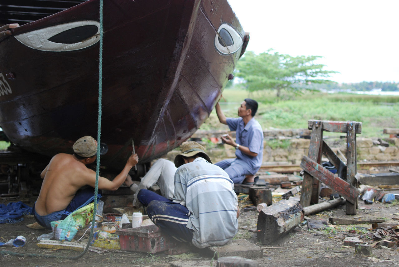 Traditional boat building in Hoi An, Vietnam Boat Building Building Casual Clothing Craft Day Holding Leisure Activity Lifestyles Making Men Outdoors Painting Person Sitting Togetherness