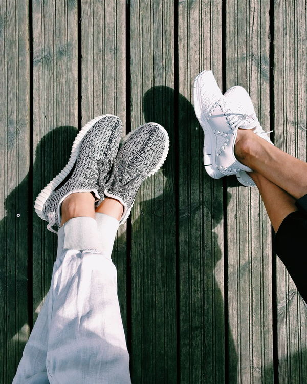 His and hers sneakers at a restaurant in London. Above Athleisure Birds Eye View Boardwalk Boost Comfort Day Designer  Fashion Heat High End His And Hers Inneva Kicks Legs Lifestyle Lifestyles Nike Out Of The Box Shoe Sneakerhead  Sneakers Streetwear Wood - Material Yeezy