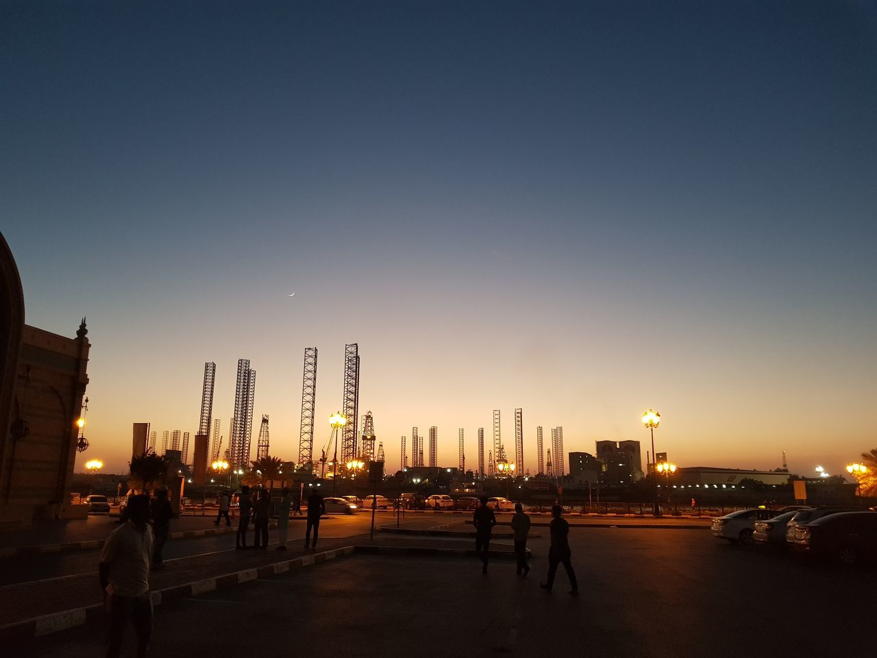 architecture, sunset, built structure, building exterior, city, skyscraper, real people, sky, clear sky, men, cityscape, lifestyles, travel destinations, illuminated, outdoors, women, modern, urban skyline, night, people