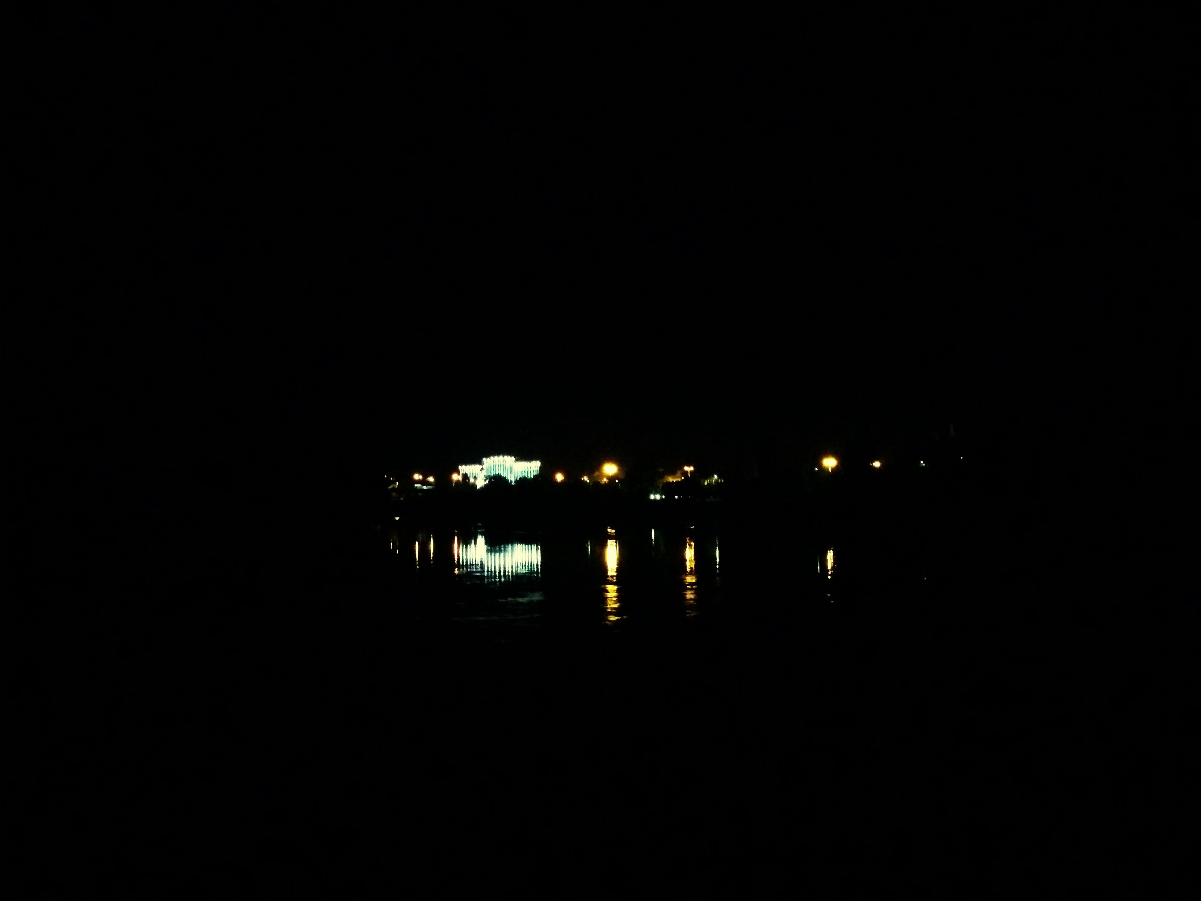 night, illuminated, water, reflection, copy space, dark, clear sky, built structure, river, architecture, waterfront, lake, tranquility, lighting equipment, street light, silhouette, outdoors, building exterior, no people, tranquil scene