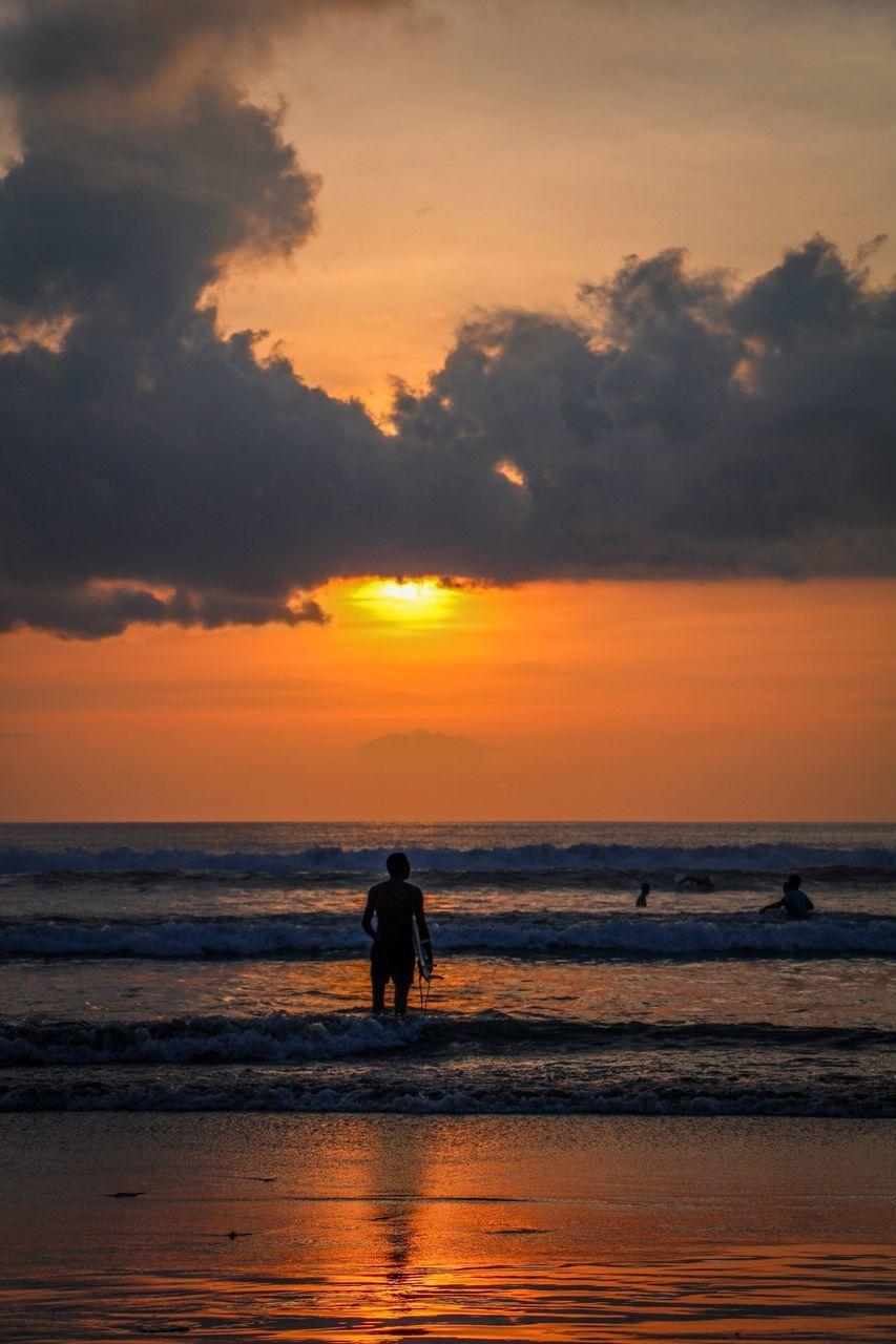 Silhouette Men On Beach Against Orange Sky