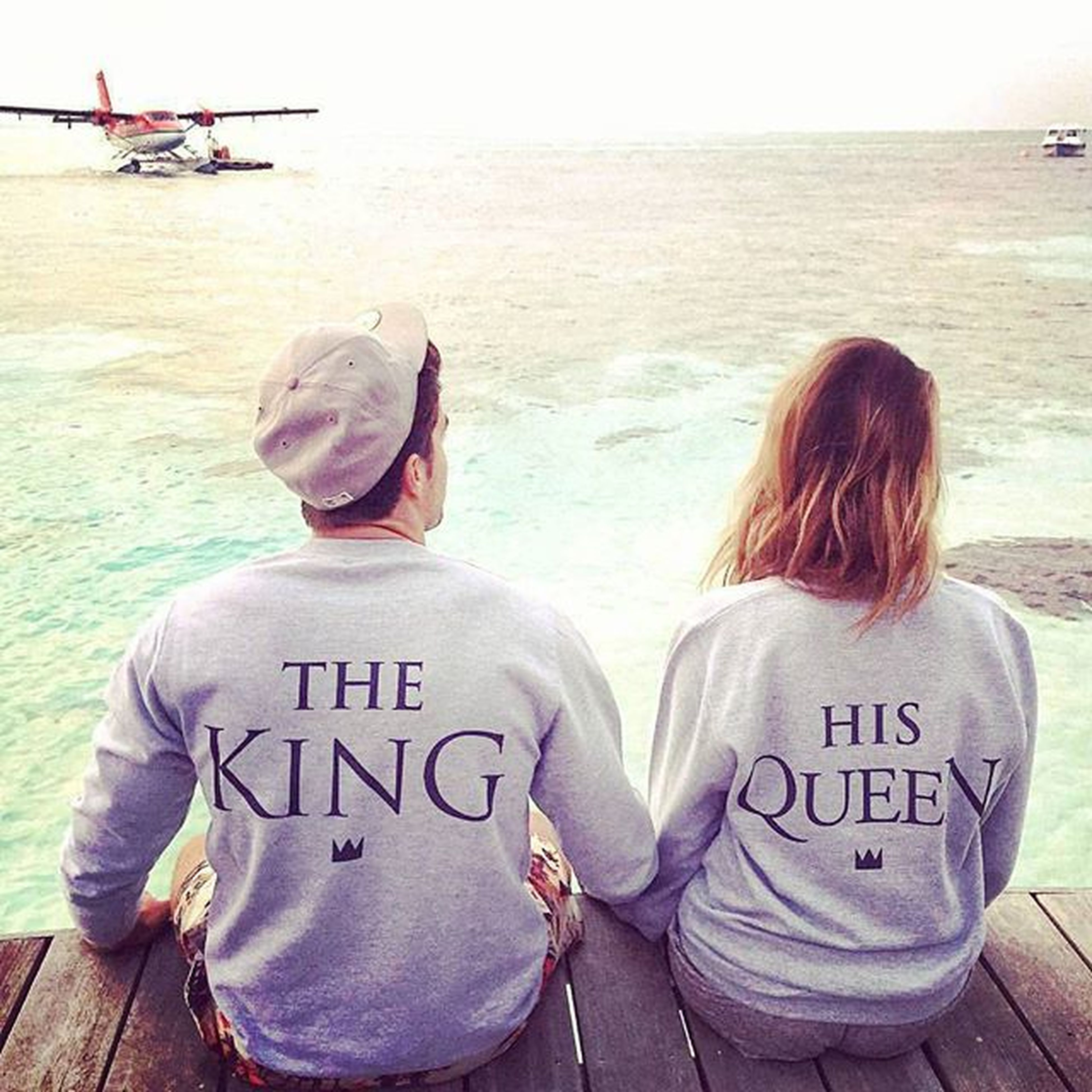water, sea, lifestyles, leisure activity, text, rear view, communication, western script, casual clothing, beach, childhood, love, togetherness, shore, bonding, sitting, men