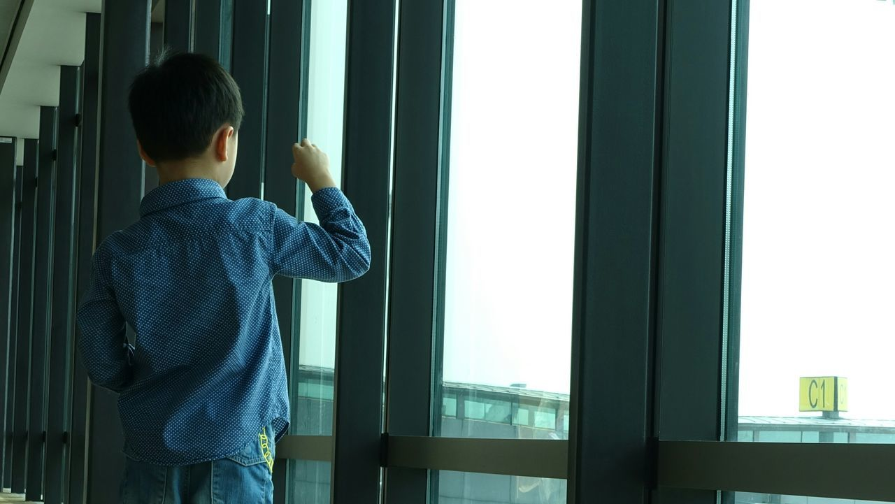 Rear View Of Boy Standing In Airport Building