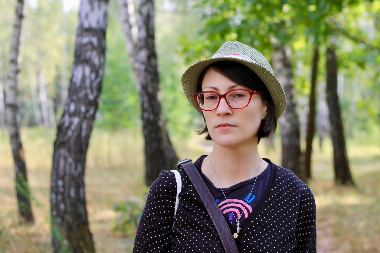 real people, leisure activity, eyeglasses, one person, front view, looking at camera, lifestyles, portrait, focus on foreground, tree trunk, forest, tree, day, standing, childhood, casual clothing, nature, outdoors, happiness, glasses, headshot, young adult, smiling, young women
