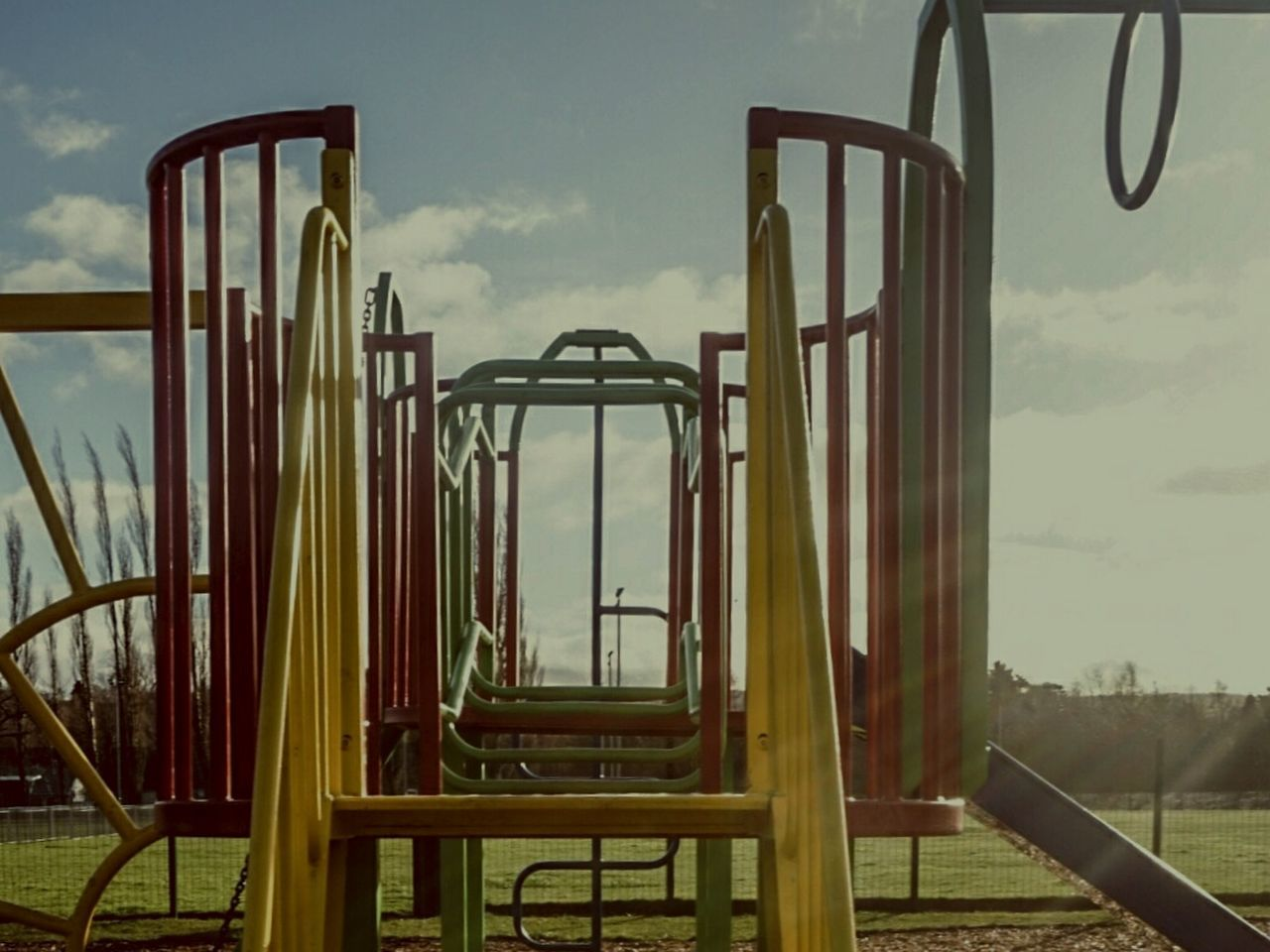 sky, playground, outdoor play equipment, metal, childhood, slide, jungle gym, outdoors, day, no people, cloud - sky, nature, merry-go-round