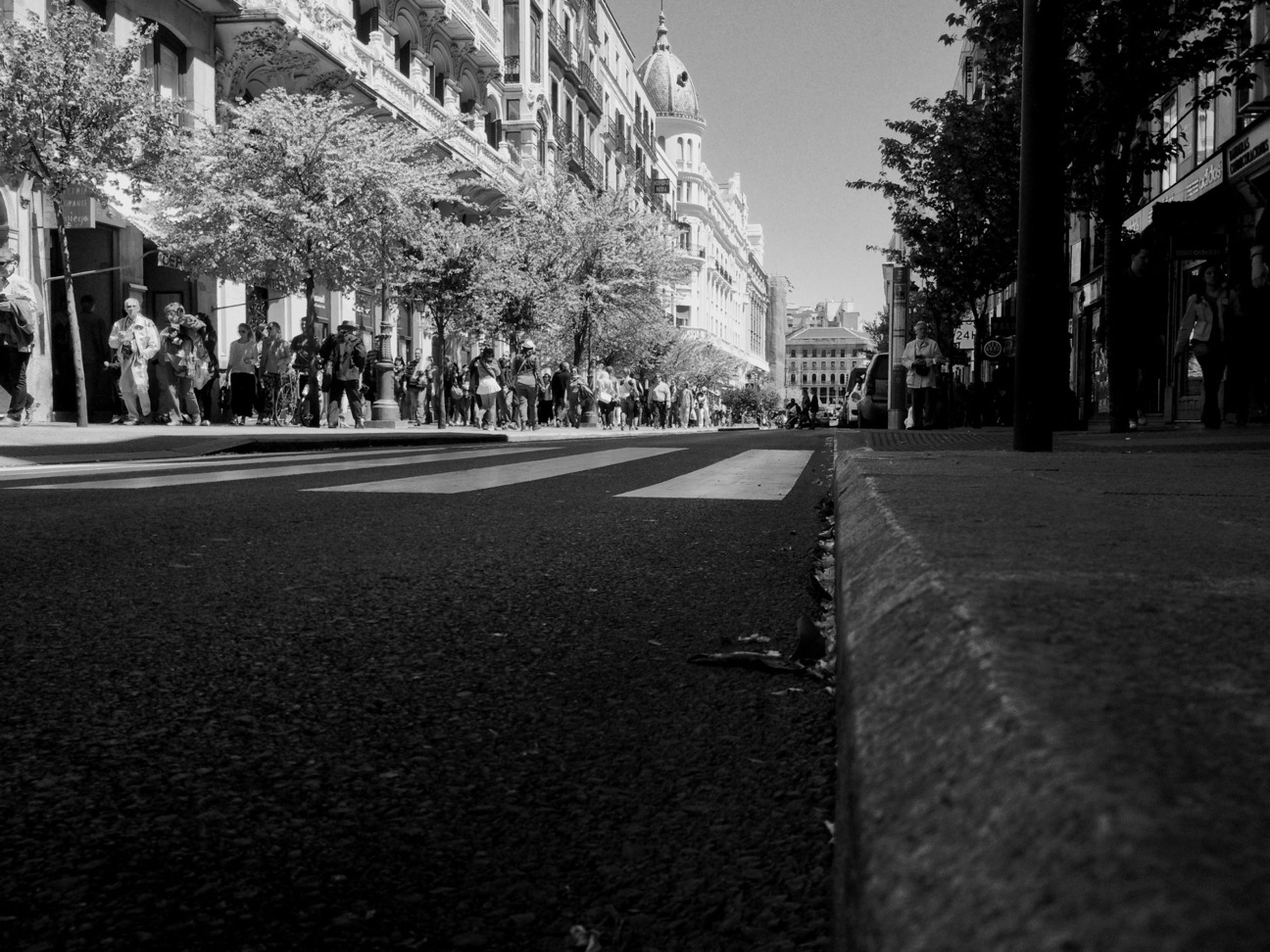 building exterior, the way forward, street, architecture, built structure, city, tree, transportation, road, diminishing perspective, vanishing point, incidental people, road marking, car, city street, city life, asphalt, building, outdoors, day