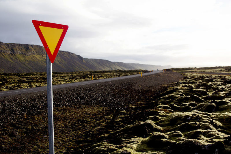 Empty road with bright sign in beautifull Iceland Desolate Destination Unknown Iceland Nature Red Sign The Road Ahead Wanderlust Beauty In Nature Break Day Landscape Moss Mountain Nature No People Outdoors Road Road Sign Scenics Sky Tranquil Scene Tranquility Travel Destinations Yellow