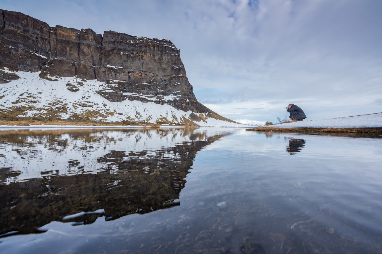 """Being the land of fire and ice, you can expect a lot of water in Iceland. We loved the way these natural mirrors gave us a different view of the countryside around us. We were constantly on the lookout for puddles, streams, and creeks. Any water that was still enough to reflect and was not frozen. (Nikon D810 14-24mm f/2.8 ƒ/8.0 14mm 1/160"""" iso 100) Adults Only Beauty In Nature Copy Space Iceland Lake Landscape Mirror Mountain Nature One Man Only One Person Only Men Outdoors People Photographer Reflection Reflection Lake Scandinavia Scenics Standing Water Travel Destinations Vacations Water Winter"""
