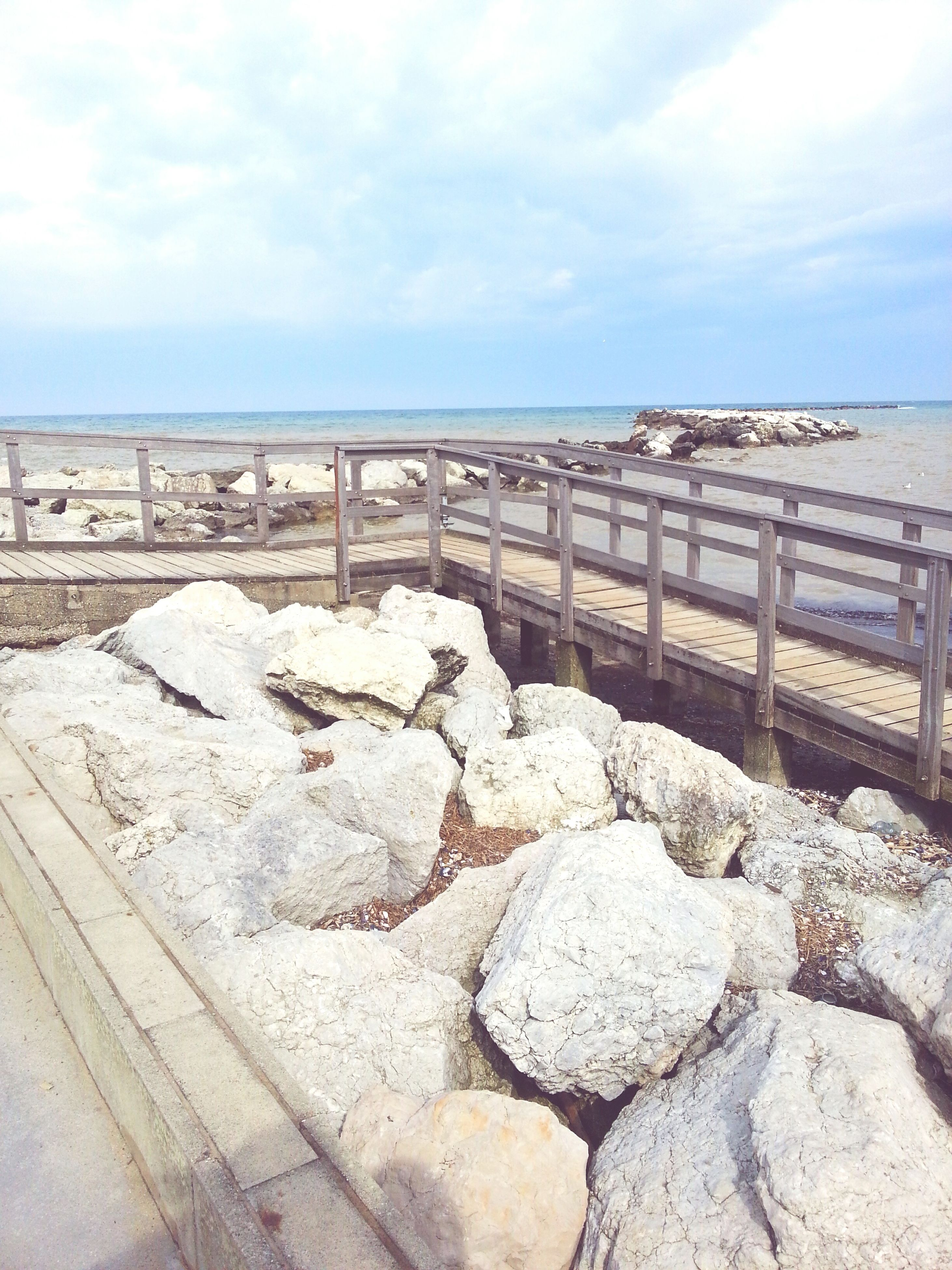 sky, cloud - sky, sea, railing, built structure, beach, water, cloud, day, nature, architecture, rock - object, tranquility, stone - object, horizon over water, tranquil scene, cloudy, outdoors, shore, scenics