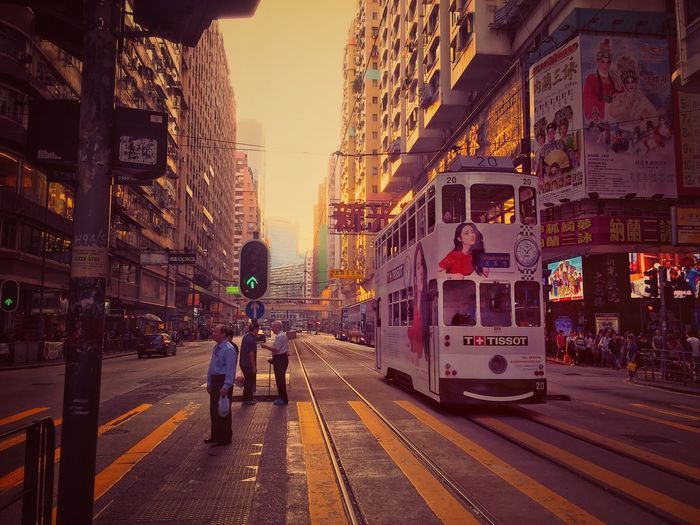 Building Exterior City Architecture Built Structure Transportation Street Land Vehicle Mode Of Transport Car City Life Outdoors Public Transportation Travel Destinations Road Men Sunset Sky Real People Day Adult