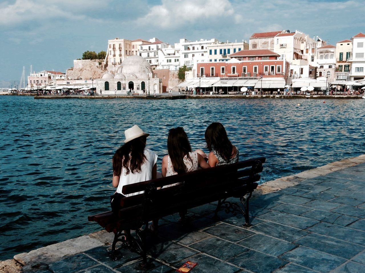 building exterior, architecture, built structure, togetherness, leisure activity, water, sitting, day, real people, two people, outdoors, women, sea, sky, men, bonding, city, young adult, adult, people, adults only