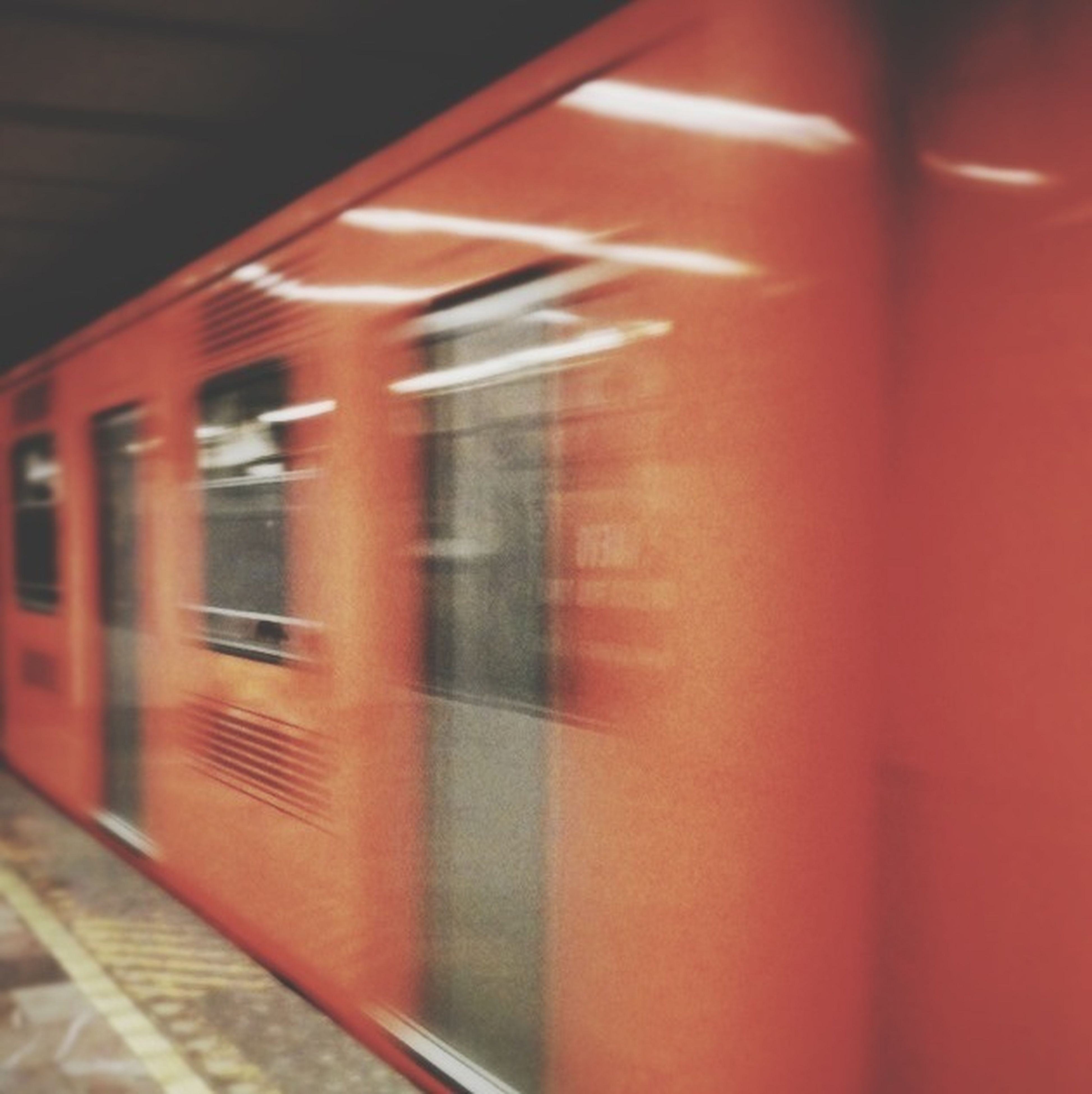 indoors, illuminated, transportation, built structure, architecture, railroad station, public transportation, rail transportation, railroad station platform, red, blurred motion, railroad track, window, wall - building feature, subway station, no people, train - vehicle, night, train, building exterior