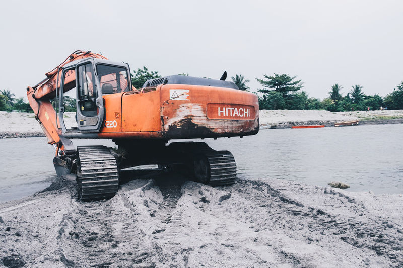 Sept. 26, 2015 - A crawler excavator at rest on the riverbank Construction Excavator Industry Machine Orange At Rest Compact Crawler Digging Equipment Excavation Foot Print Heavy Equipment Minimal Nature Operation Outdoors River Rotating Sand Sky Transportation Truck Vehicle Illustrative Editorial in General Santos, Philippines Breathing Space Investing In Quality Of Life The Week On EyeEm