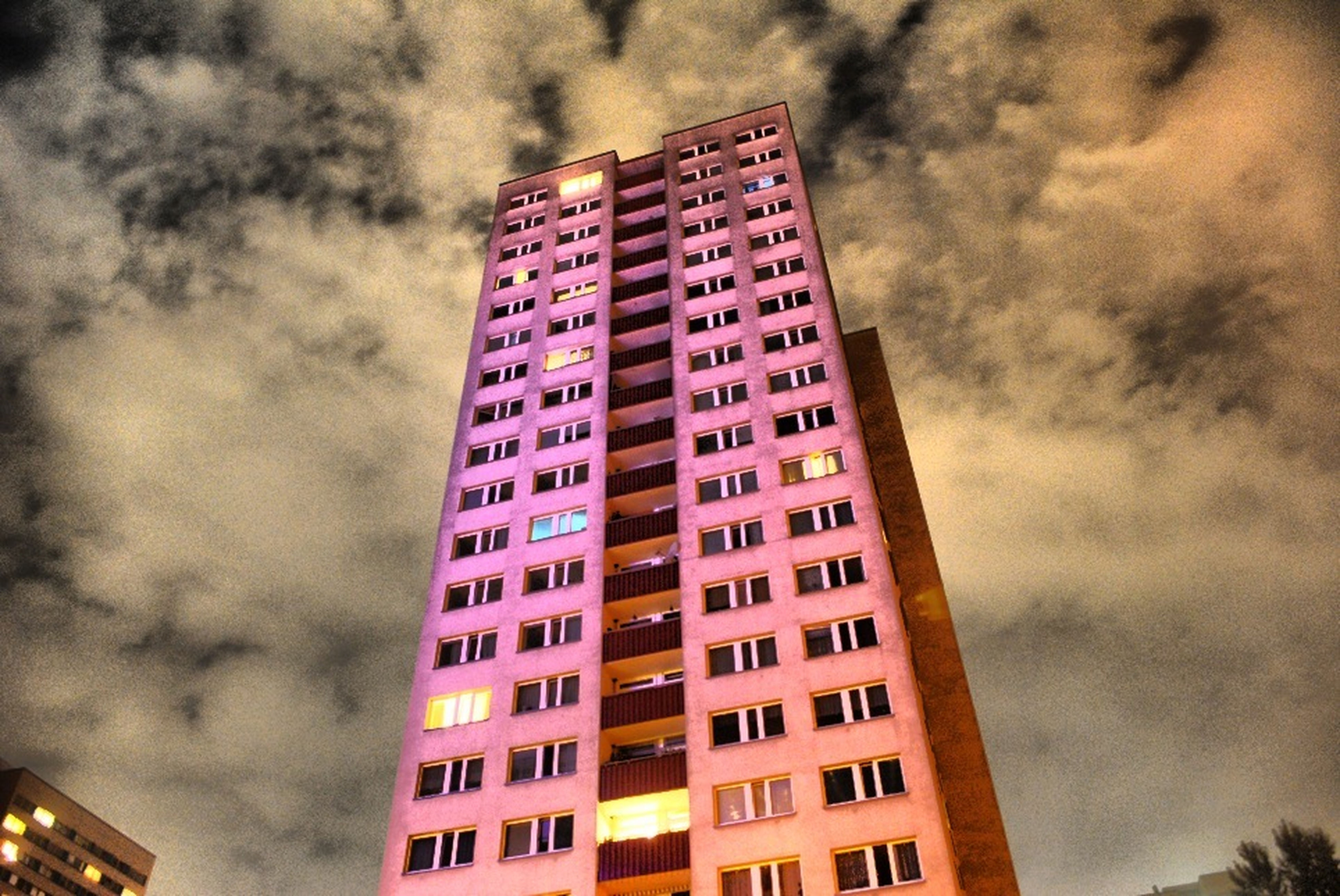 architecture, building exterior, built structure, low angle view, sky, cloud - sky, city, cloudy, building, overcast, residential building, weather, modern, tall - high, residential structure, skyscraper, dusk, outdoors, cloud, tower