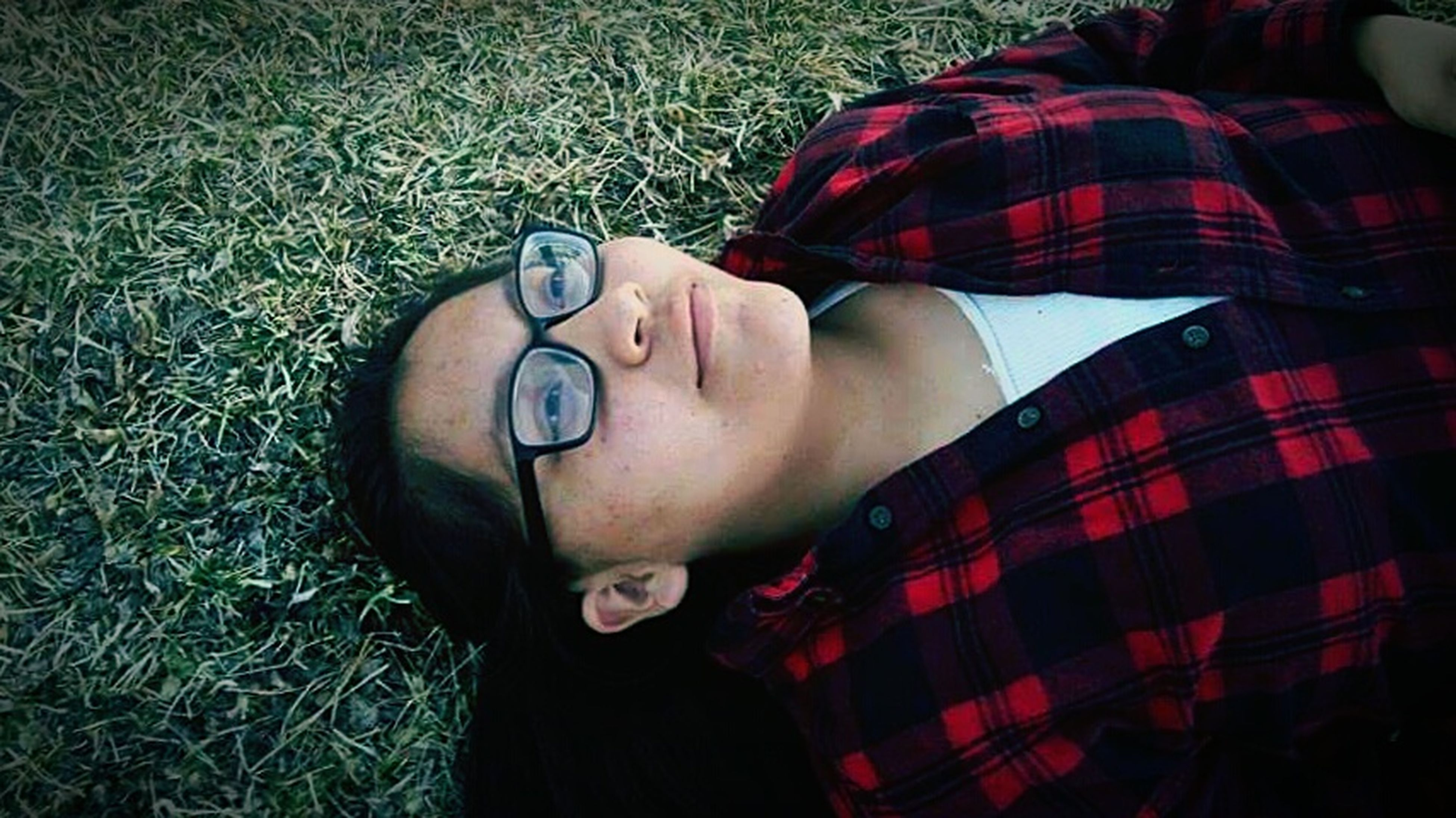 lying down, relaxation, eyes closed, beauty, listening, eyeglasses, one person, grass, people, leisure activity, adults only, young adult, happiness, young women, day, one woman only, adult, portrait, only women, silence, outdoors, human body part, one young woman only