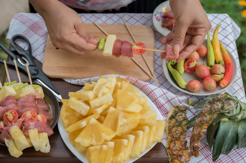 Barbecue BBQ Close-up Day Food Food Preparation Freshness Healthy Eating High Angle View Holding Human Body Part Human Hand Lifestyles One Person People Pineapple Preparing Food Real People Skewer Skewered Food Table