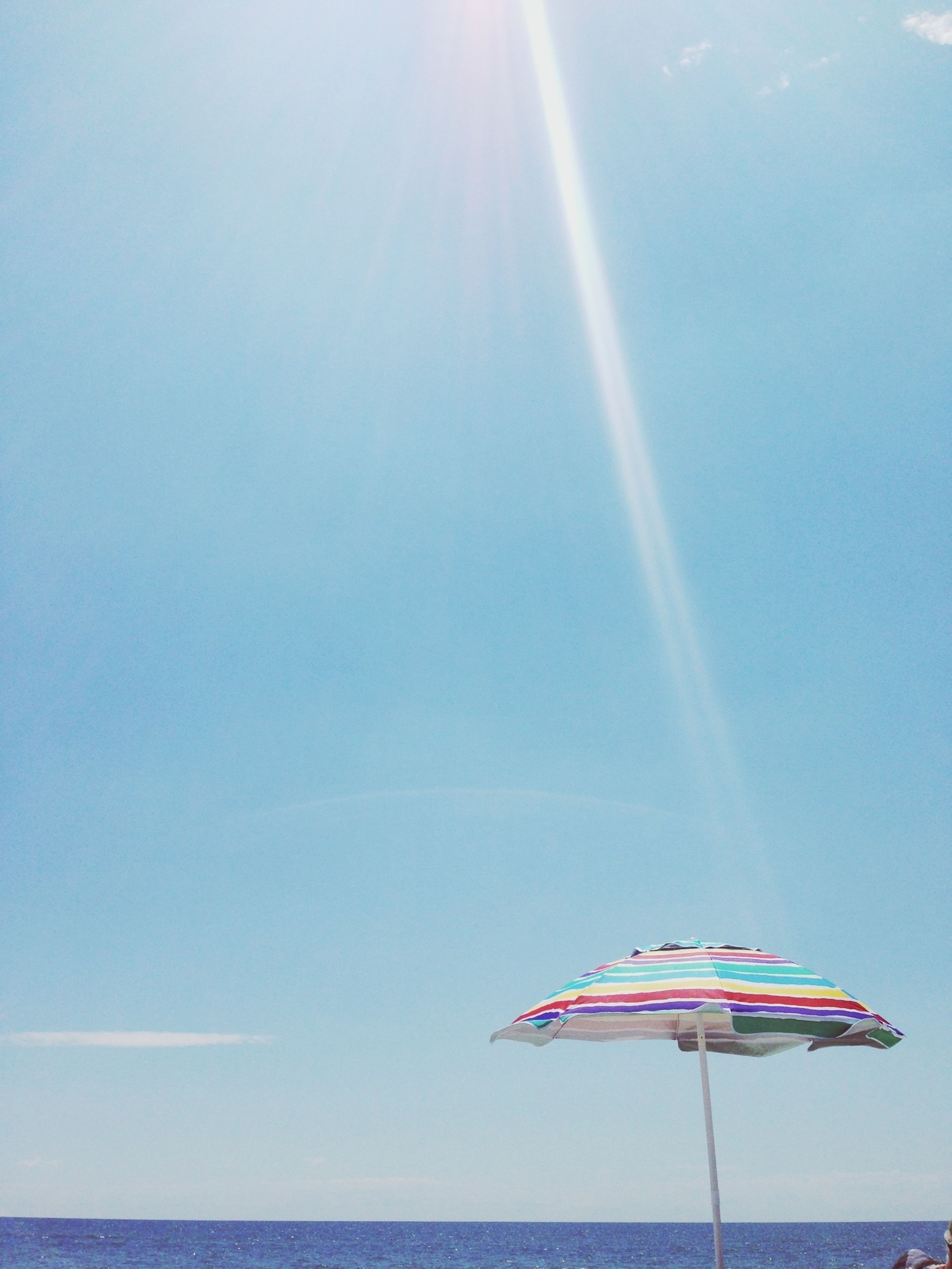 sky, blue, water, transportation, sea, clear sky, mid-air, sun, sunlight, flying, low angle view, horizon over water, nature, scenics, beauty in nature, copy space, mode of transport, day, sunbeam, nautical vessel