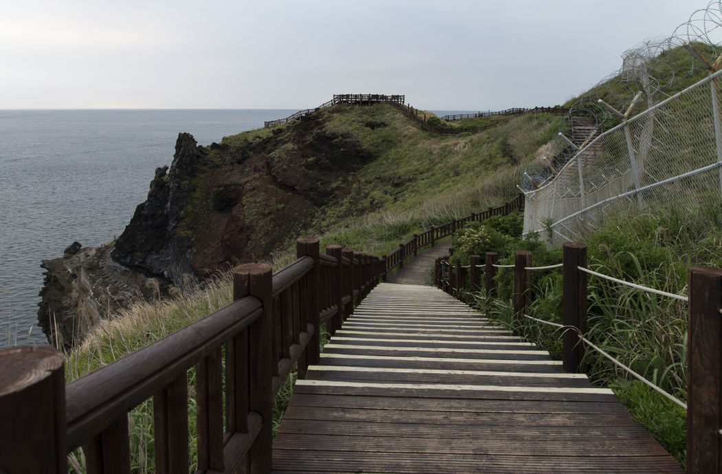 landscape at Songaksan in Jeju Island, South Korea Beauty In Nature Built Structure Day Footbridge Grass Horizon Over Water JEJU ISLAND  Nature No People Outdoors Railing Scenics Sea Seaside Sky Songaksan The Way Forward Tranquil Scene Tranquility Water Wood - Material Wood Paneling