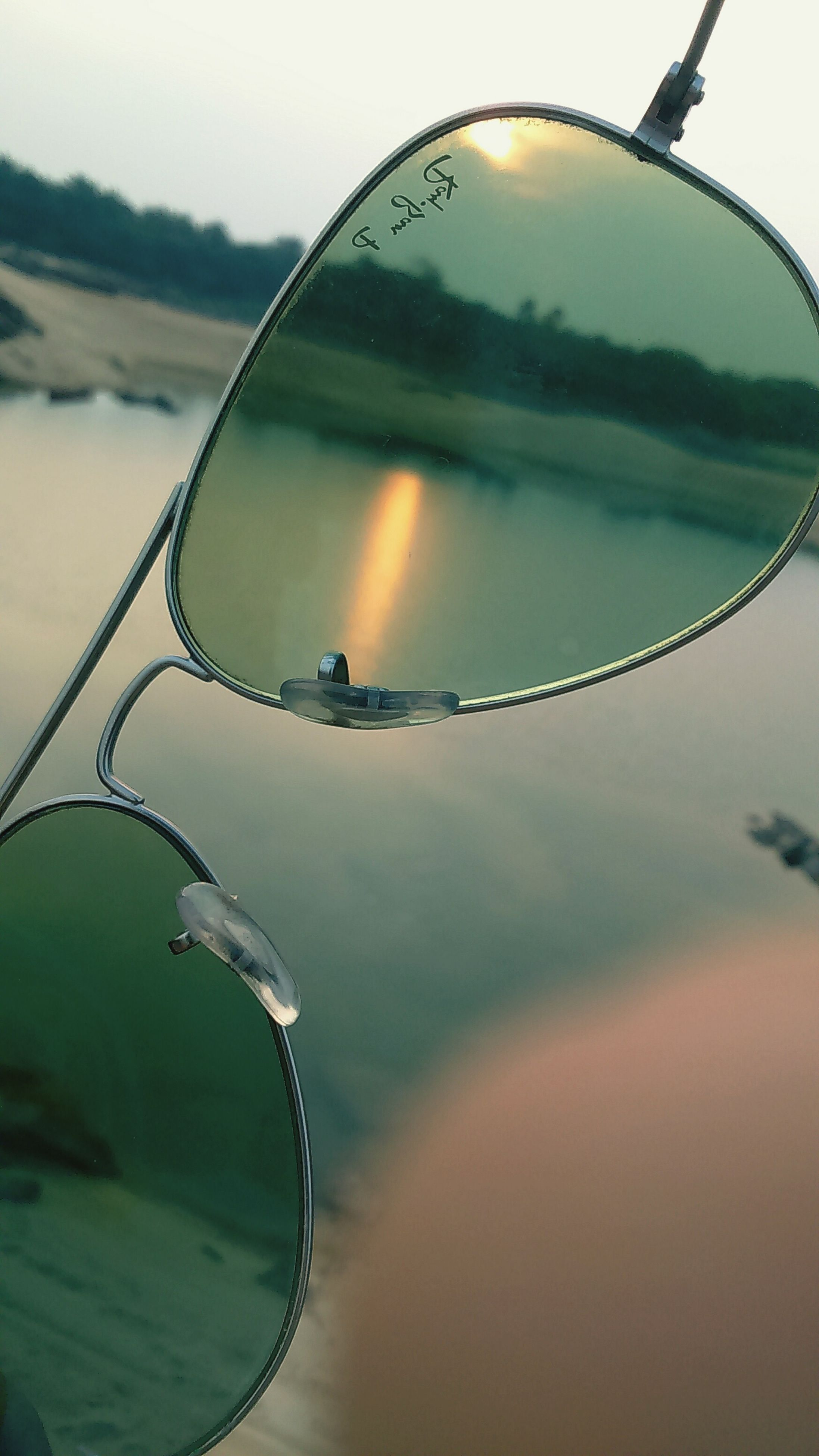 focus on foreground, close-up, circle, reflection, mid-air, sky, nature, sunset, transportation, sport, beauty in nature, sphere, tranquility, outdoors, water, part of, no people, landscape, day, selective focus