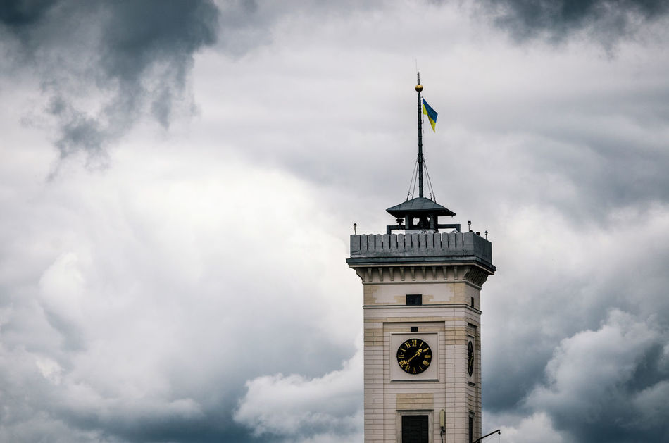 City hall clock tower of Lviv with Ukrainian flag at the top against the stormy cloudy sky, Ukraine. Concept of the restlessly or courage and power Architecture Building Exterior Built Structure City Hall Clock Tower Cloud - Sky Flag Low Angle View Lviv No People Outdoors Patriotism Sky Storm Tower Ukraine Ukrainian