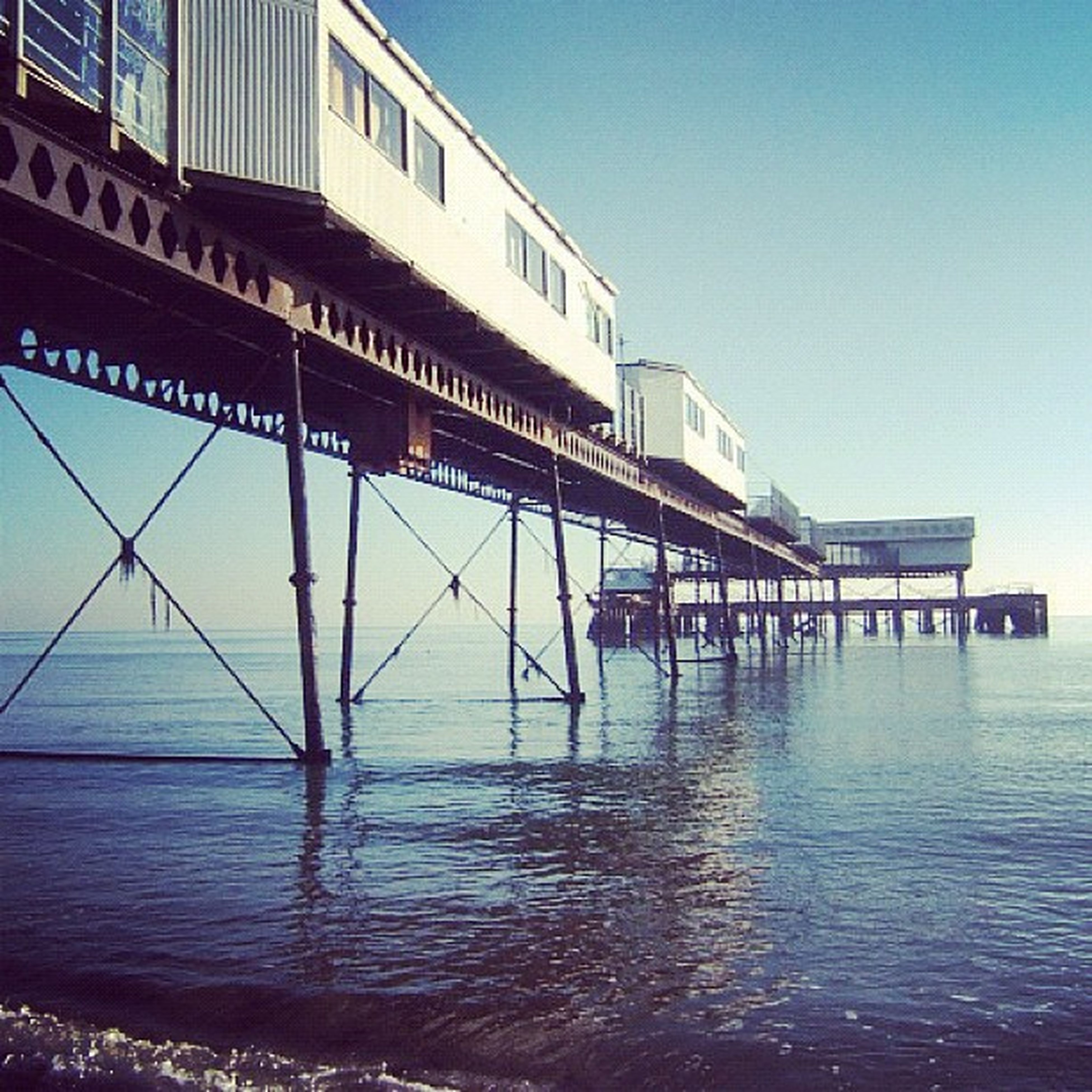 built structure, water, architecture, clear sky, sea, waterfront, blue, building exterior, sky, reflection, day, pier, rippled, low angle view, copy space, horizon over water, outdoors, no people, connection, nature