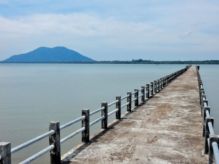 Water Tranquil Scene Scenics Mountain Tranquility Sea The Way Forward Beauty In Nature Railing In A Row Nature Sky Mountain Range Blue Long Diminishing Perspective Non-urban Scene Shore Day Ocean Bridge Jetty