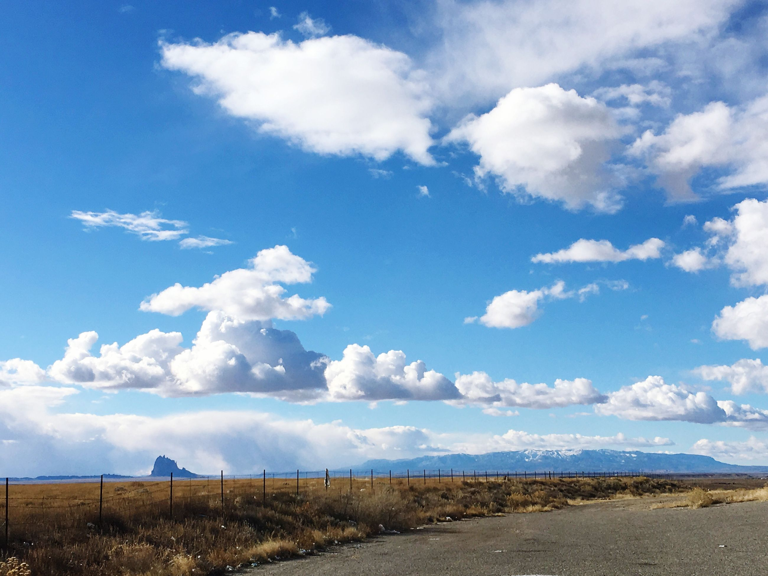 sky, tranquil scene, tranquility, landscape, blue, cloud - sky, scenics, field, cloud, nature, beauty in nature, grass, road, cloudy, day, horizon over land, non-urban scene, water, remote, outdoors
