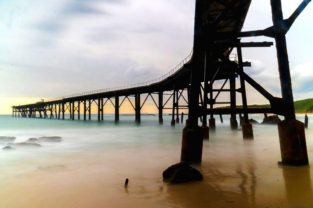 Silhouette Bridge Over Sea Against Sky