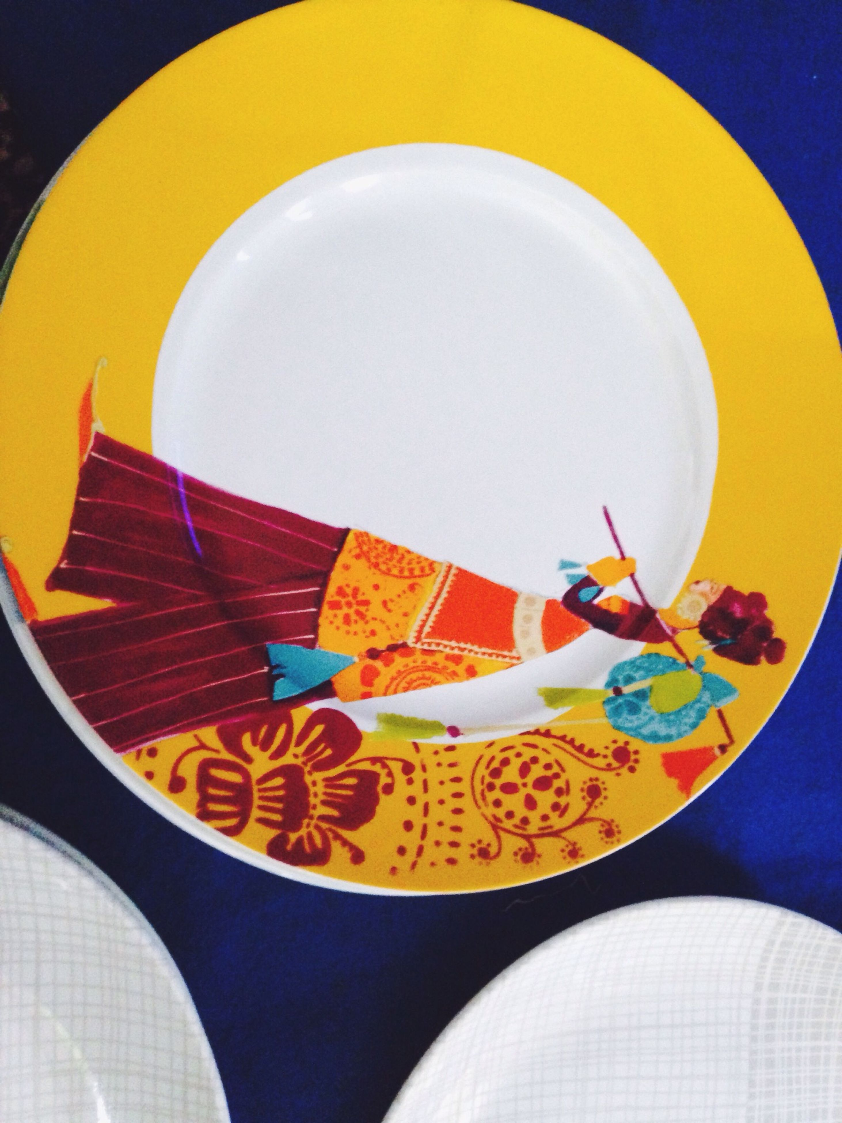indoors, still life, blue, multi colored, yellow, circle, table, close-up, plate, creativity, high angle view, art and craft, no people, directly above, food and drink, pattern, art, bowl, studio shot, design
