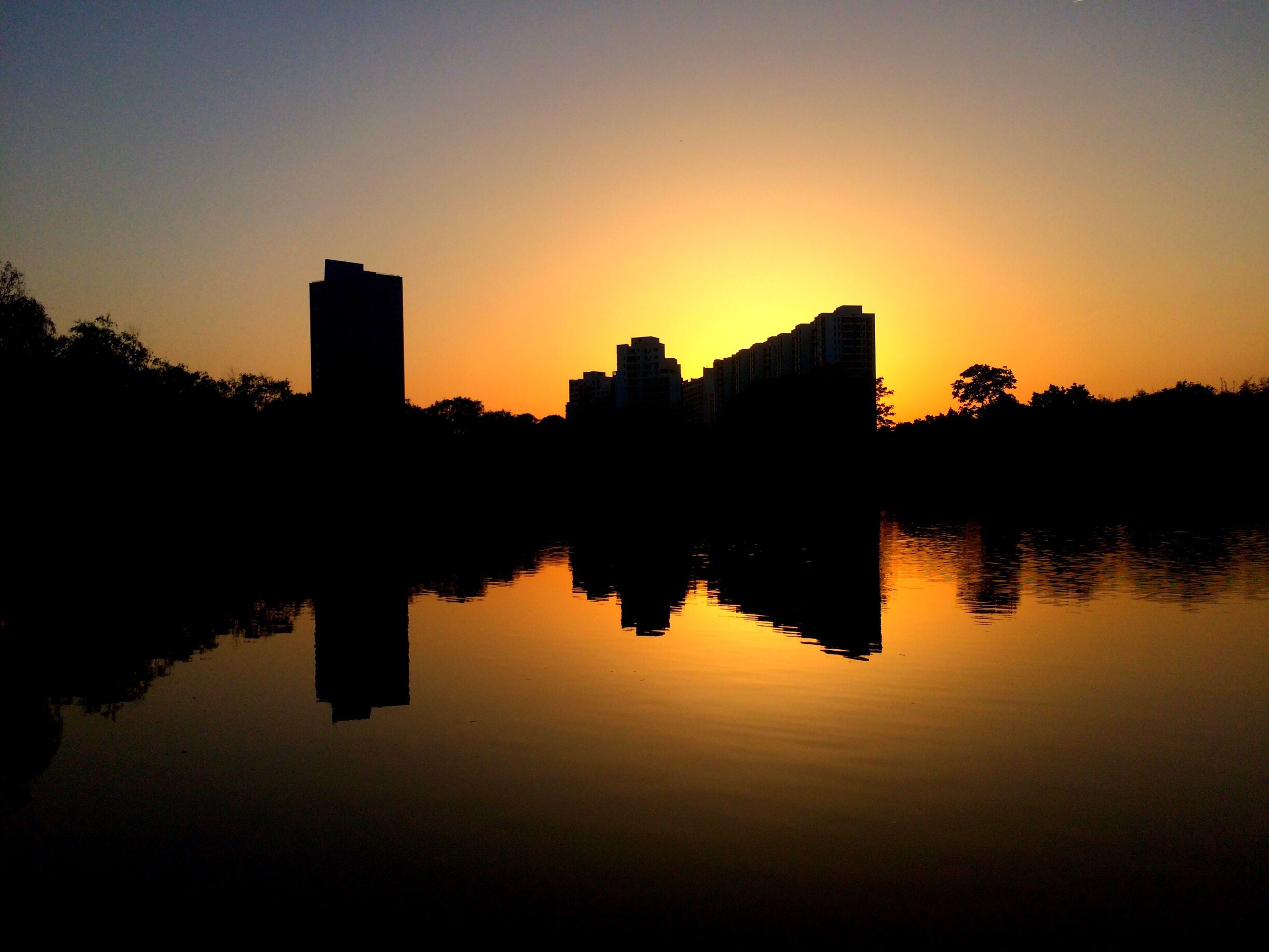 reflection, sunset, silhouette, architecture, water, built structure, building exterior, waterfront, sky, no people, tree, lake, clear sky, outdoors, symmetry, nature, beauty in nature, city
