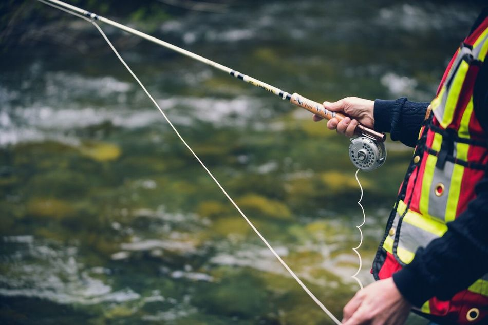A man pulls line from his Fly Fishing rod on the Little Qualicum River on Vancouver Island Bc Canada