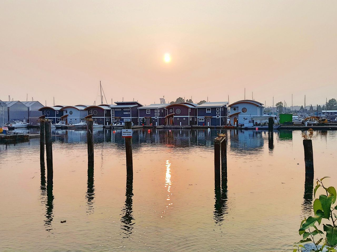 water, reflection, sunset, nautical vessel, moored, built structure, nature, outdoors, harbor, mode of transport, sea, sky, sun, waterfront, wooden post, tranquility, beauty in nature, transportation, architecture, tranquil scene, sunlight, stilt house, no people, scenics, travel destinations, building exterior, clear sky, day