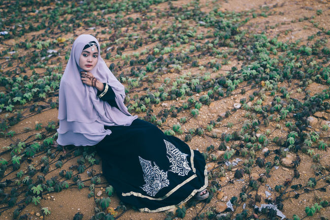 Portrait Young Women Sitting Field Looking At Camera Outdoors Person Hijab Fashion Non-urban Scene Portrait Of A Woman Rural Scene Day Alone People People And Places Mood Girl Nature Young Adult Warm Clothing Autumn Fashionable
