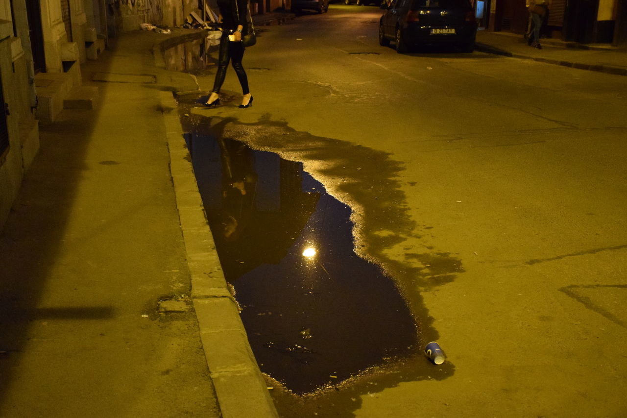 incidental people, water, outdoors, real people, architecture, built structure, city, road, puddle, nature, day, one person, people