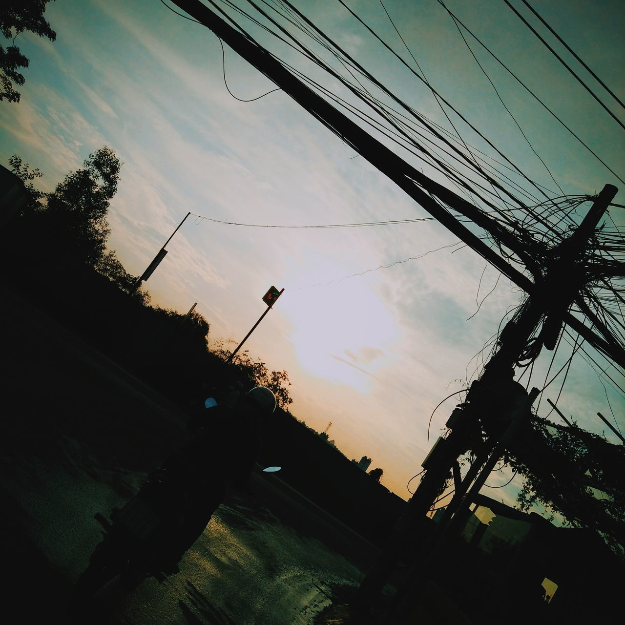 cable, sky, power line, silhouette, connection, sunset, low angle view, tree, cloud - sky, no people, electricity pylon, power supply, transportation, technology, outdoors, day, telephone line, nature, road sign, architecture