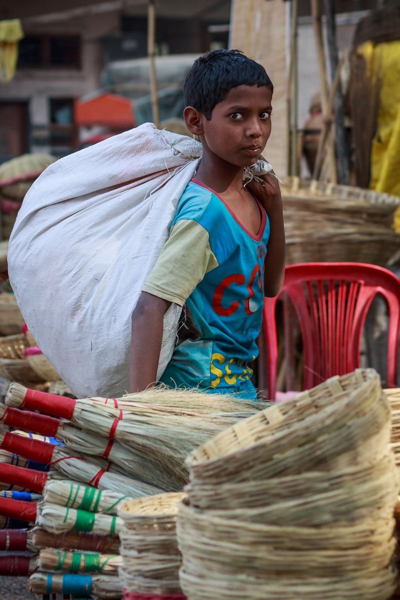 Bamboo Crafter's Son Carrying a Bag of Raw Material. Pune, India. Traditional Clothing Black Hair One Person One Woman Only Cultures Only Women Adults Only Outdoors People Adult Sari Day What Who Where