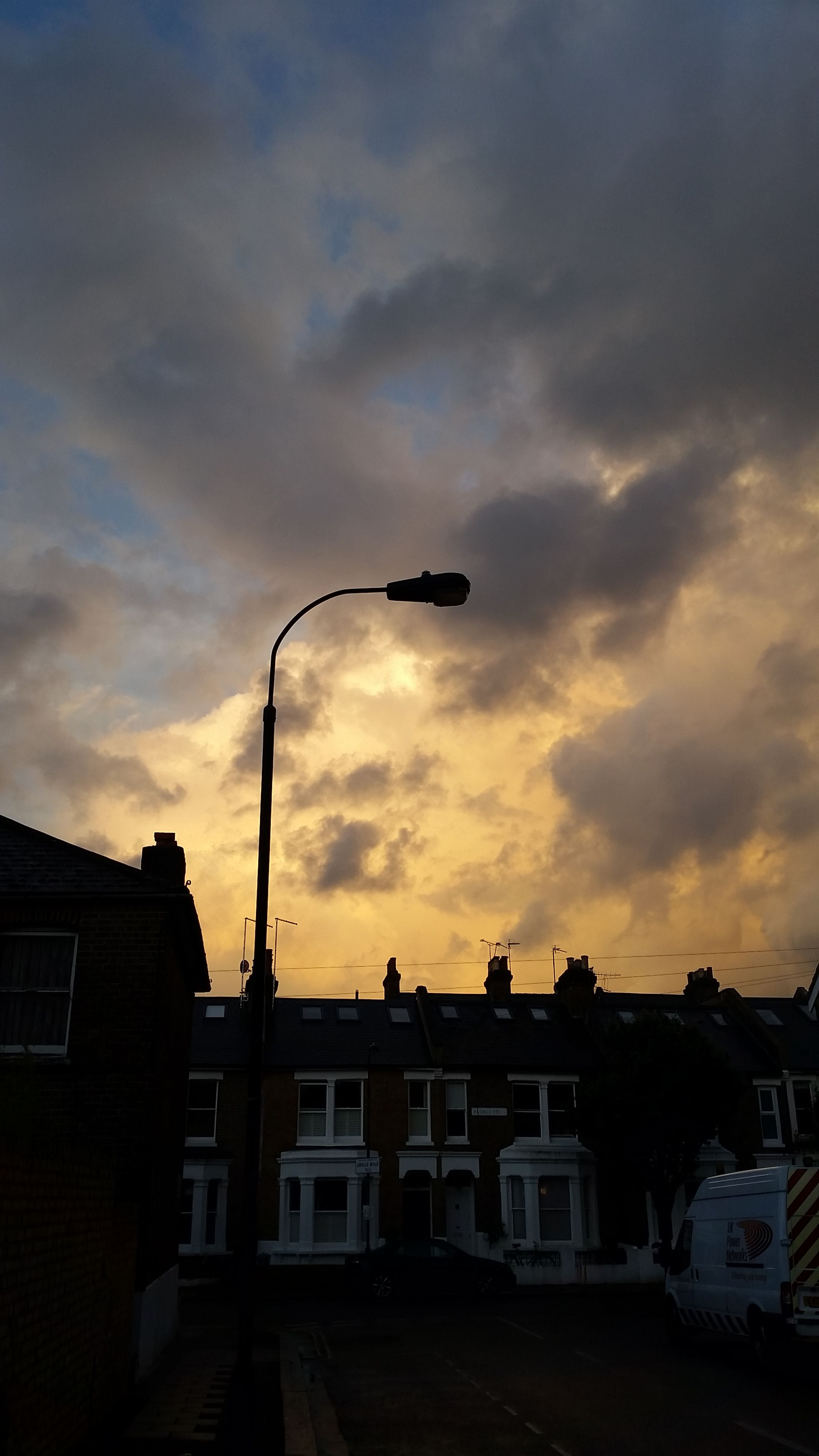 building exterior, architecture, built structure, sky, low angle view, cloud - sky, cloudy, cloud, building, sunset, silhouette, city, residential structure, residential building, dusk, outdoors, street light, no people, house, high section
