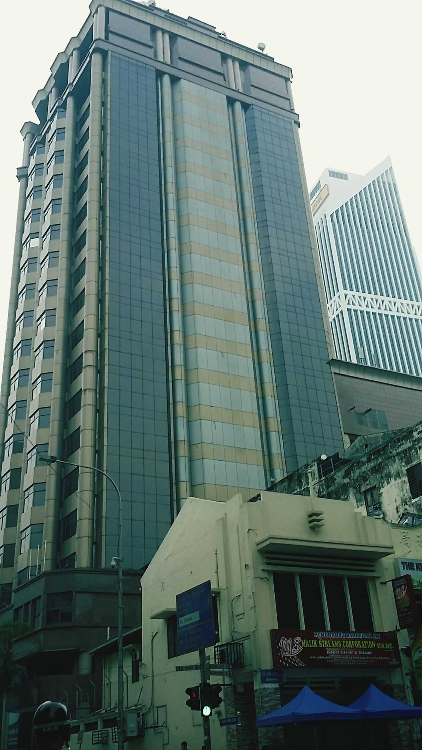 building exterior, architecture, built structure, low angle view, city, office building, building, modern, skyscraper, tall - high, window, glass - material, tower, sky, clear sky, residential building, day, outdoors, city life, no people