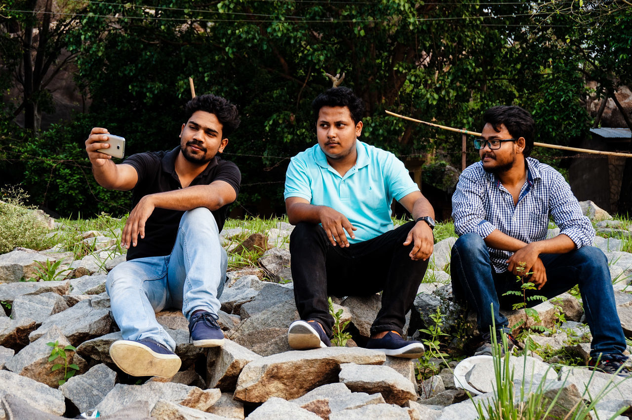 sitting, casual clothing, mid adult, mid adult men, outdoors, young men, smiling, rock - object, full length, tree, front view, only men, adults only, young adult, real people, relaxation, day, togetherness, happiness, male friendship, cheerful, looking at camera, adult, portrait, people, plant, friendship, men, nature
