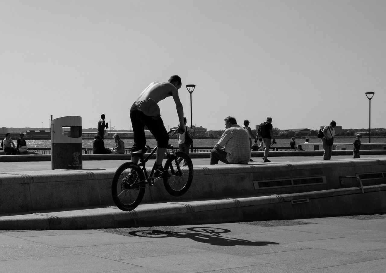 bicycle, real people, clear sky, leisure activity, men, cycling, skateboard park, day, outdoors, transportation, sunlight, lifestyles, sky, women, large group of people, stunt, full length, skill, sport, bmx cycling, extreme sports, city, sportsman, people, adult