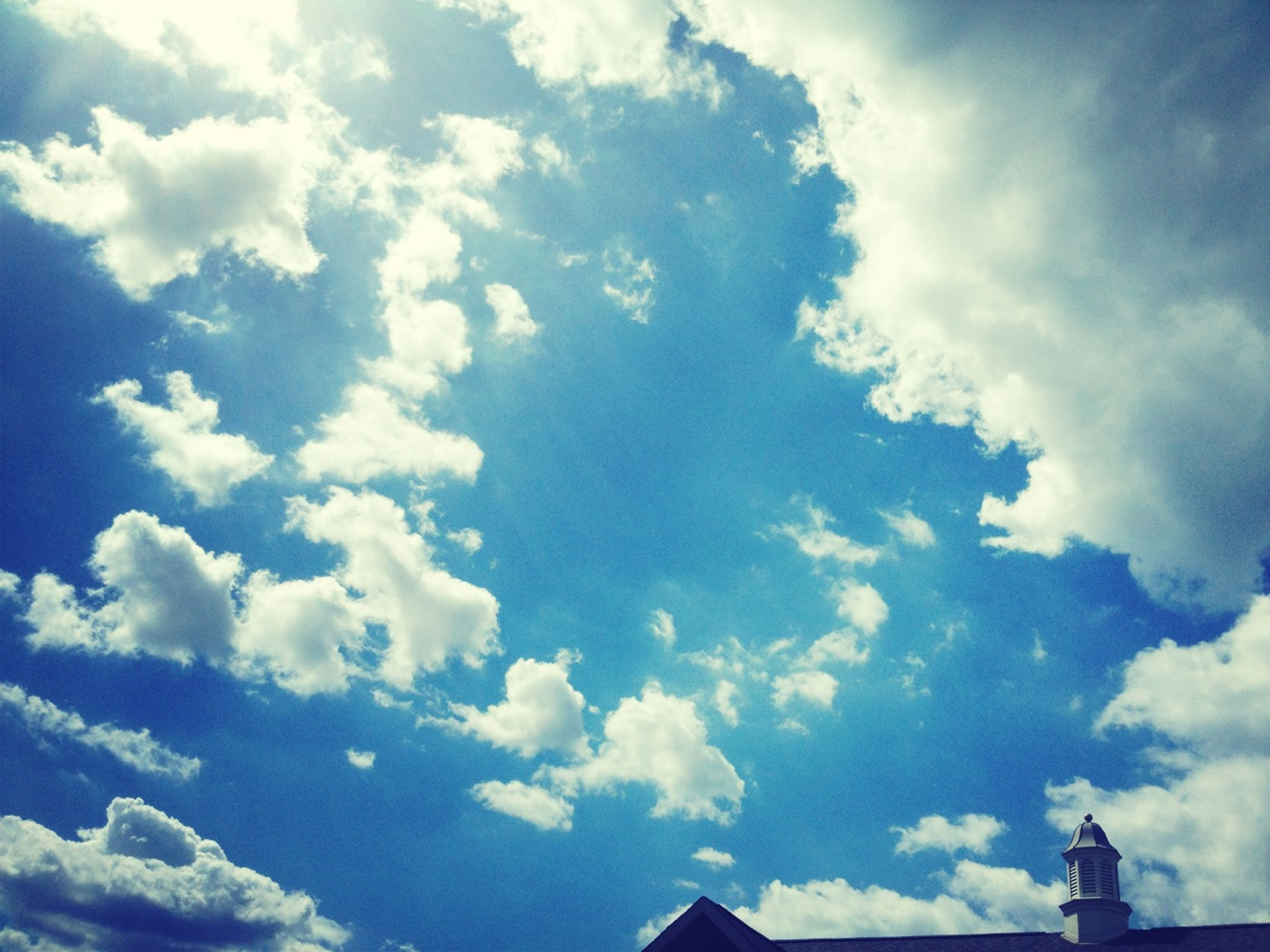 low angle view, sky, cloud - sky, blue, cloud, cloudy, high section, day, built structure, outdoors, no people, nature, architecture, sunlight, building exterior, cloudscape, beauty in nature, tranquility, silhouette, white color