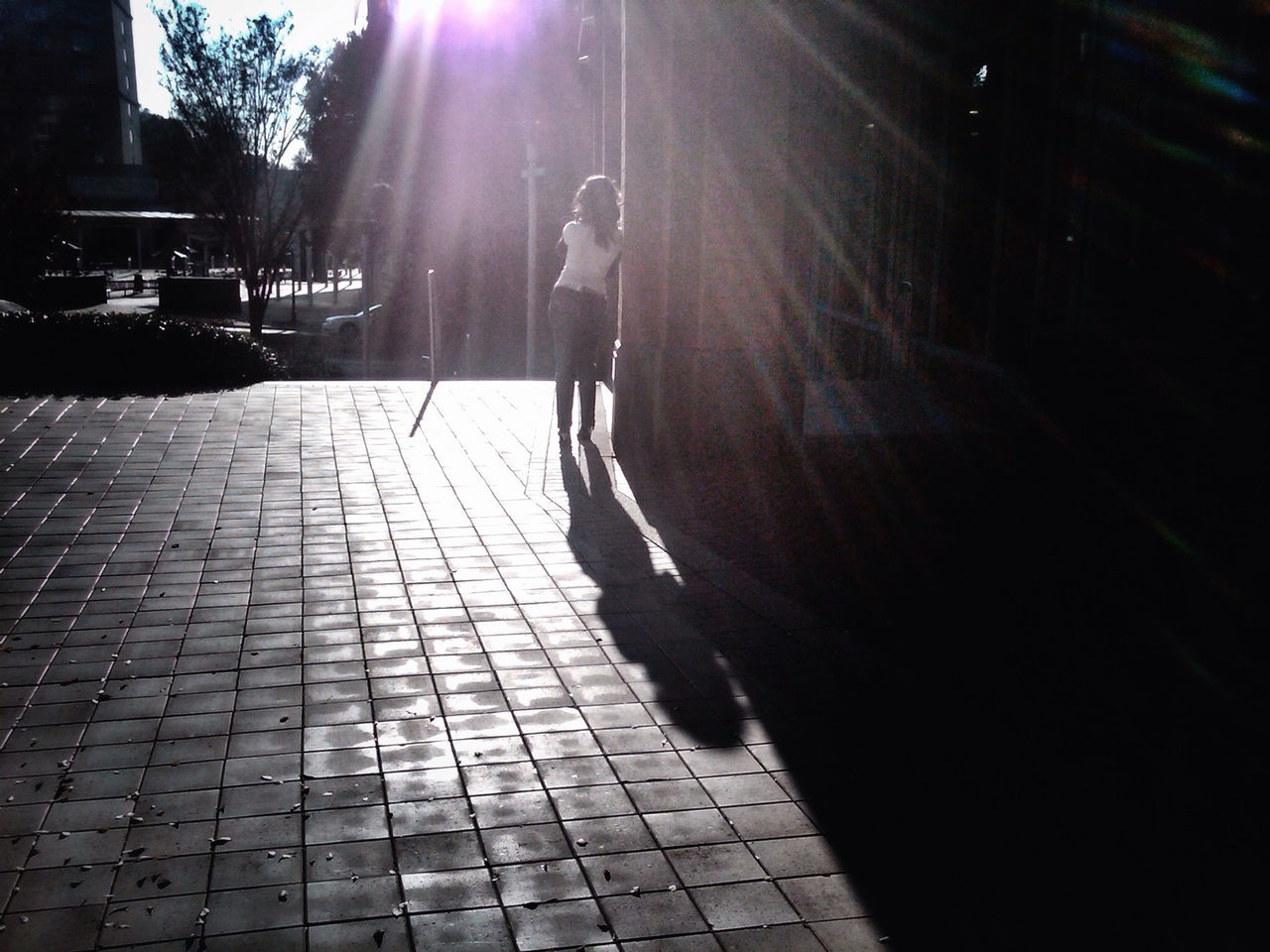sunlight, full length, shadow, sunbeam, real people, one person, walking, leisure activity, lifestyles, day, standing, women, outdoors, young adult, people