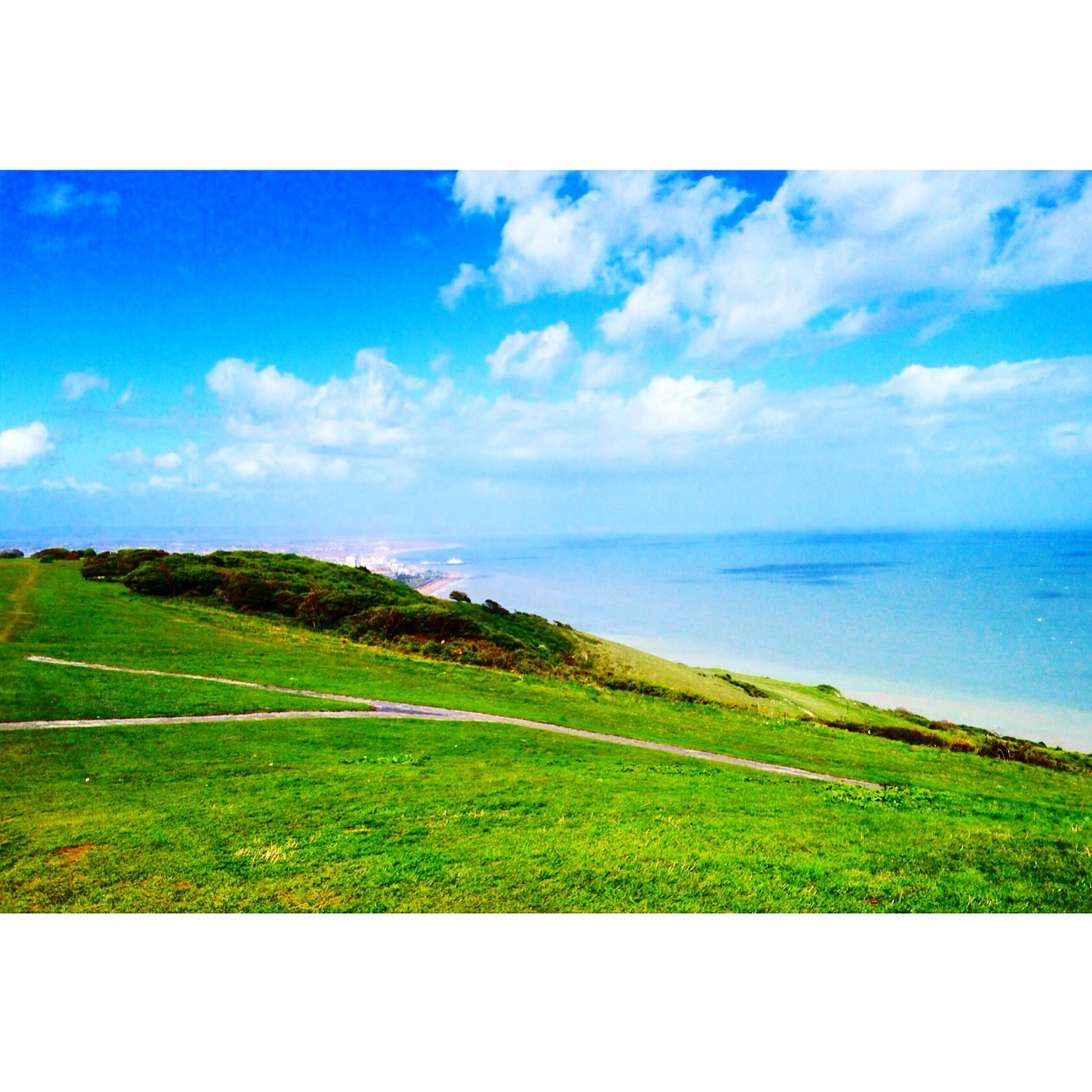 tranquil scene, grass, tranquility, sky, scenics, transfer print, beauty in nature, blue, landscape, horizon over water, nature, green color, field, sea, auto post production filter, cloud, cloud - sky, water, idyllic, horizon over land