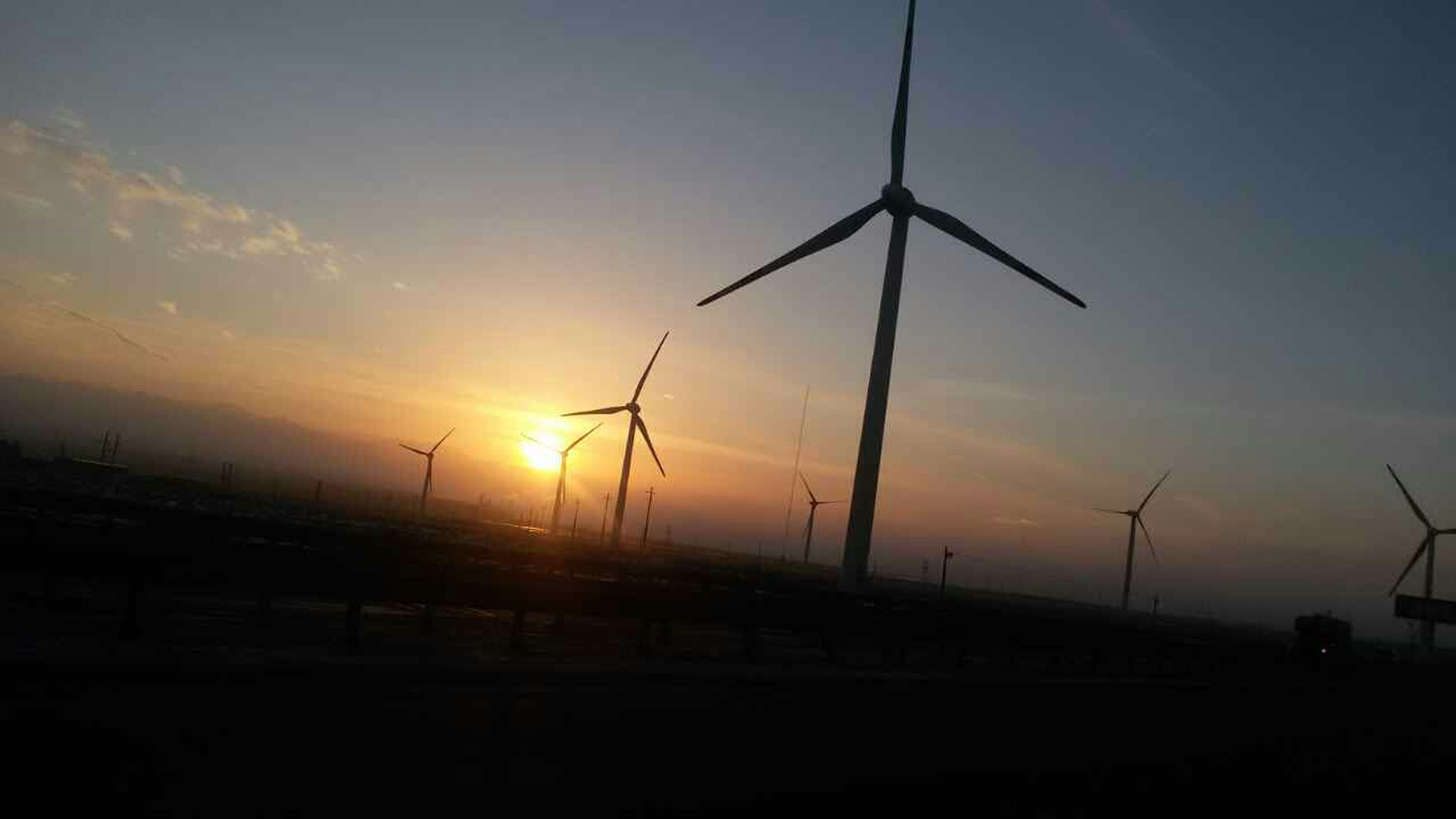 sunset, silhouette, fuel and power generation, sky, wind turbine, sun, alternative energy, wind power, environmental conservation, landscape, orange color, windmill, nature, tranquility, renewable energy, transportation, scenics, tranquil scene, beauty in nature, electricity pylon