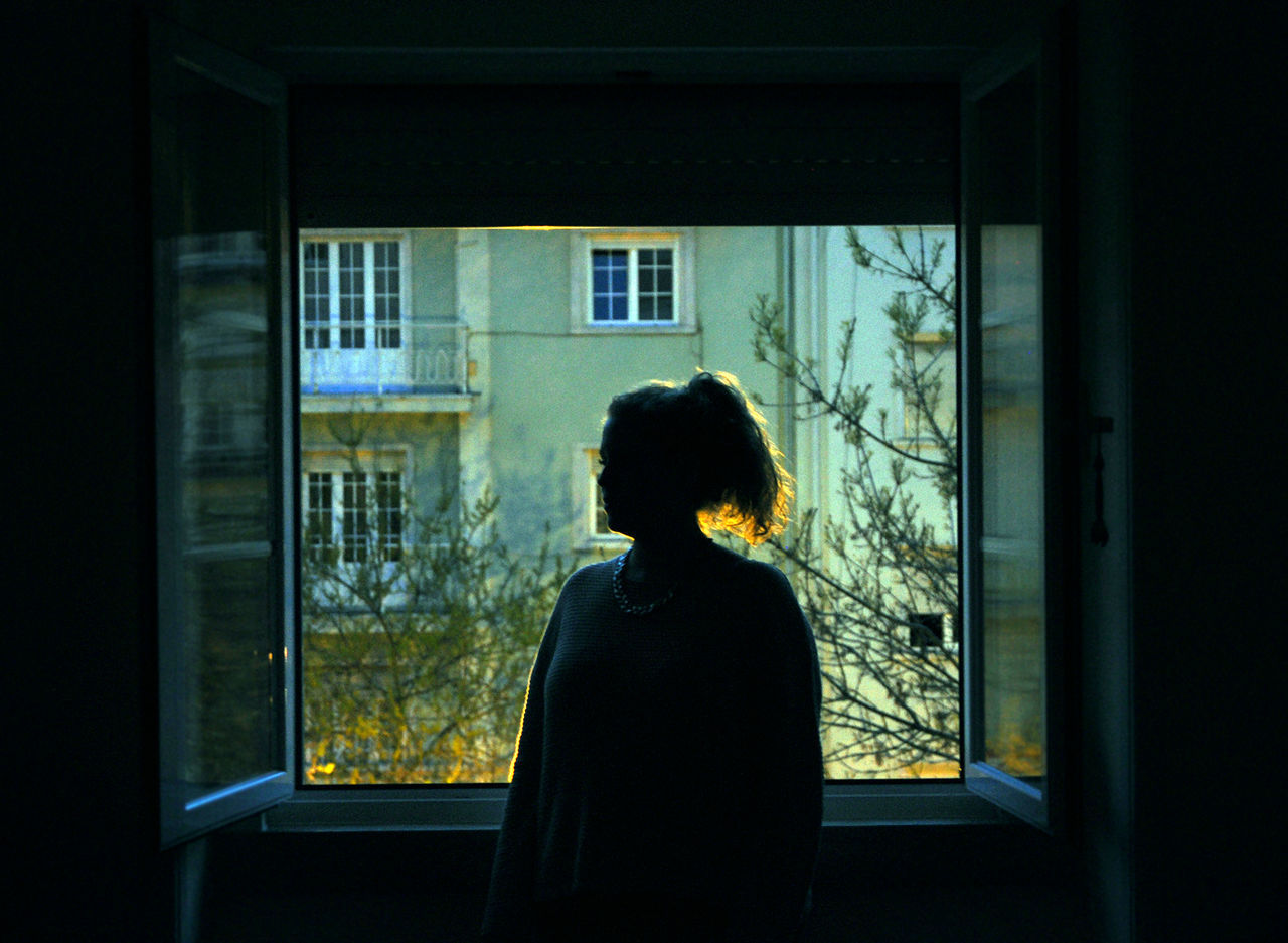real people, window, rear view, one person, women, looking through window, lifestyles, indoors, leisure activity, standing, architecture, day