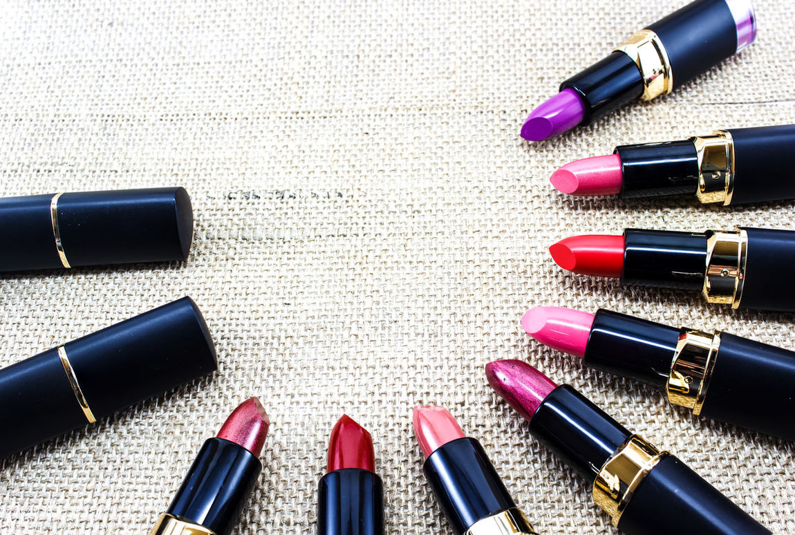 Lipstick colors on a fabric background to form a page border Background Beauty Black Border Care Colors Coral Cosmetics Edge Flat Golden Lay Lippy Lips Lipstick Make Makeup Page Pink Product Purple Red Set Stick Up