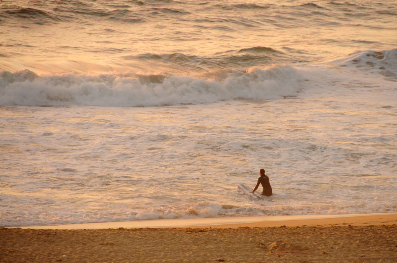 Rear View Of Surfer At Beach During Sunset
