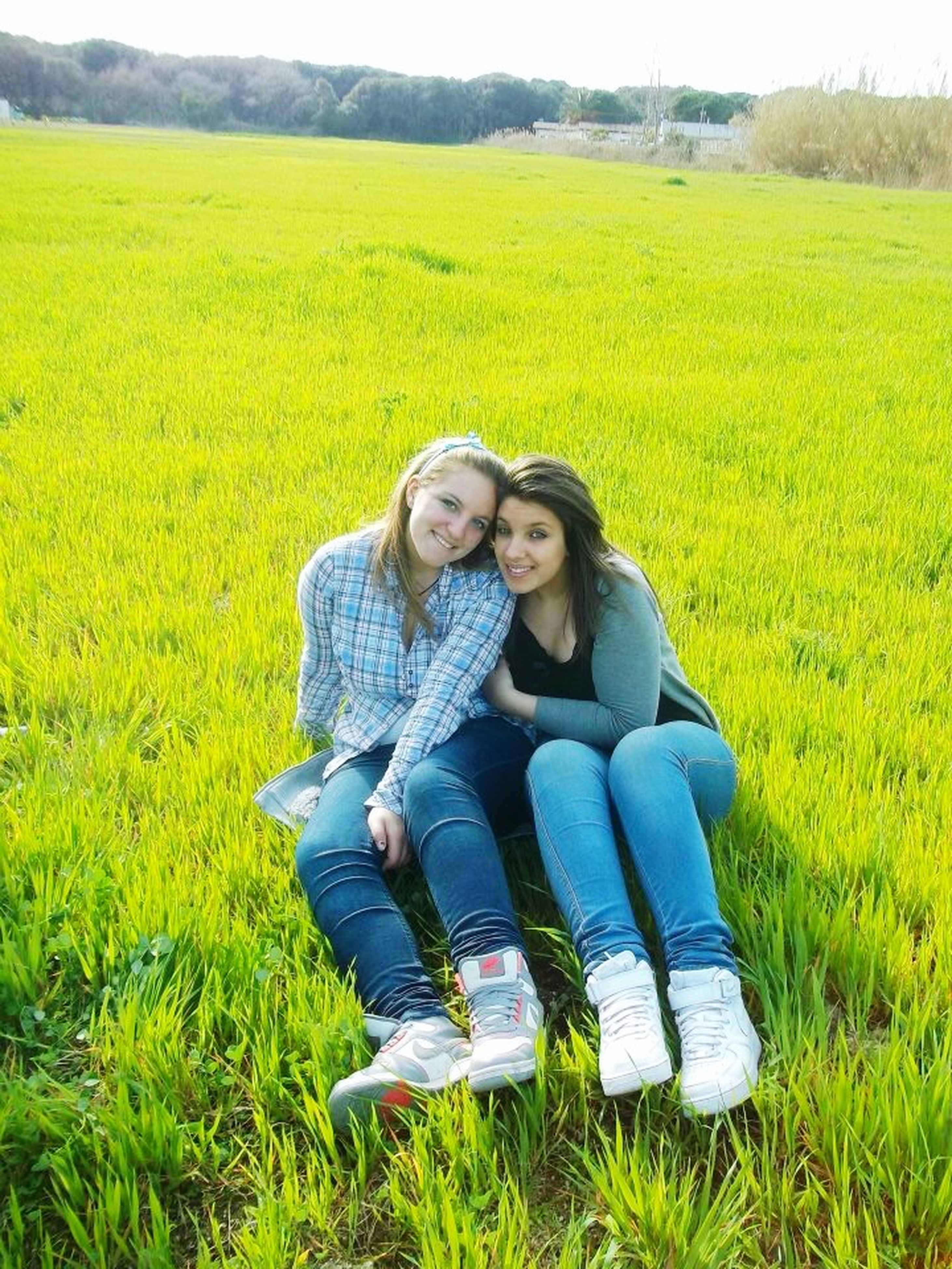 grass, field, person, casual clothing, grassy, green color, bonding, lifestyles, leisure activity, smiling, three quarter length, togetherness, sitting, landscape, growth, young adult, love, rural scene