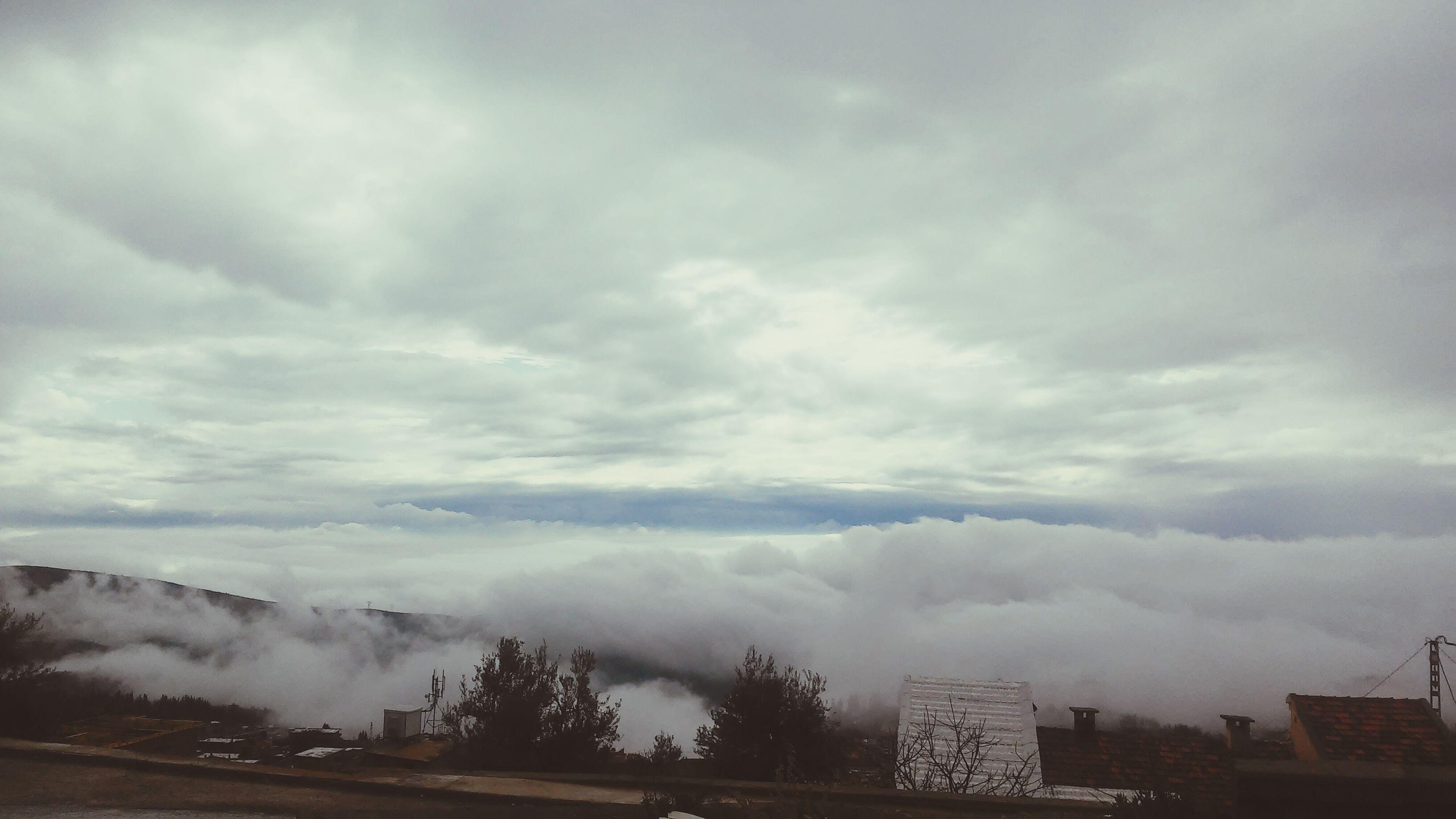 sky, cloud - sky, weather, cloudy, mountain, building exterior, overcast, scenics, beauty in nature, fog, nature, built structure, architecture, landscape, cloud, tranquility, day, tranquil scene, city, mountain range
